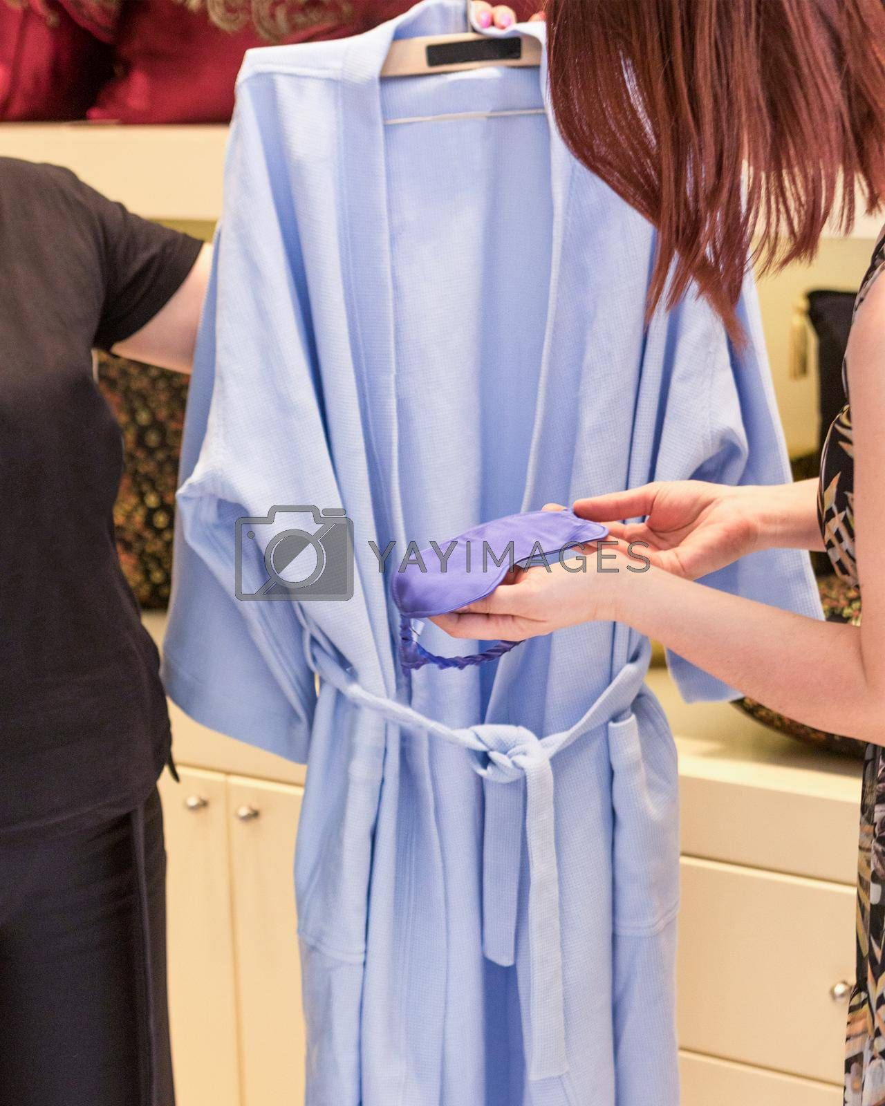 Woman holding a new robe and eye cover at the store