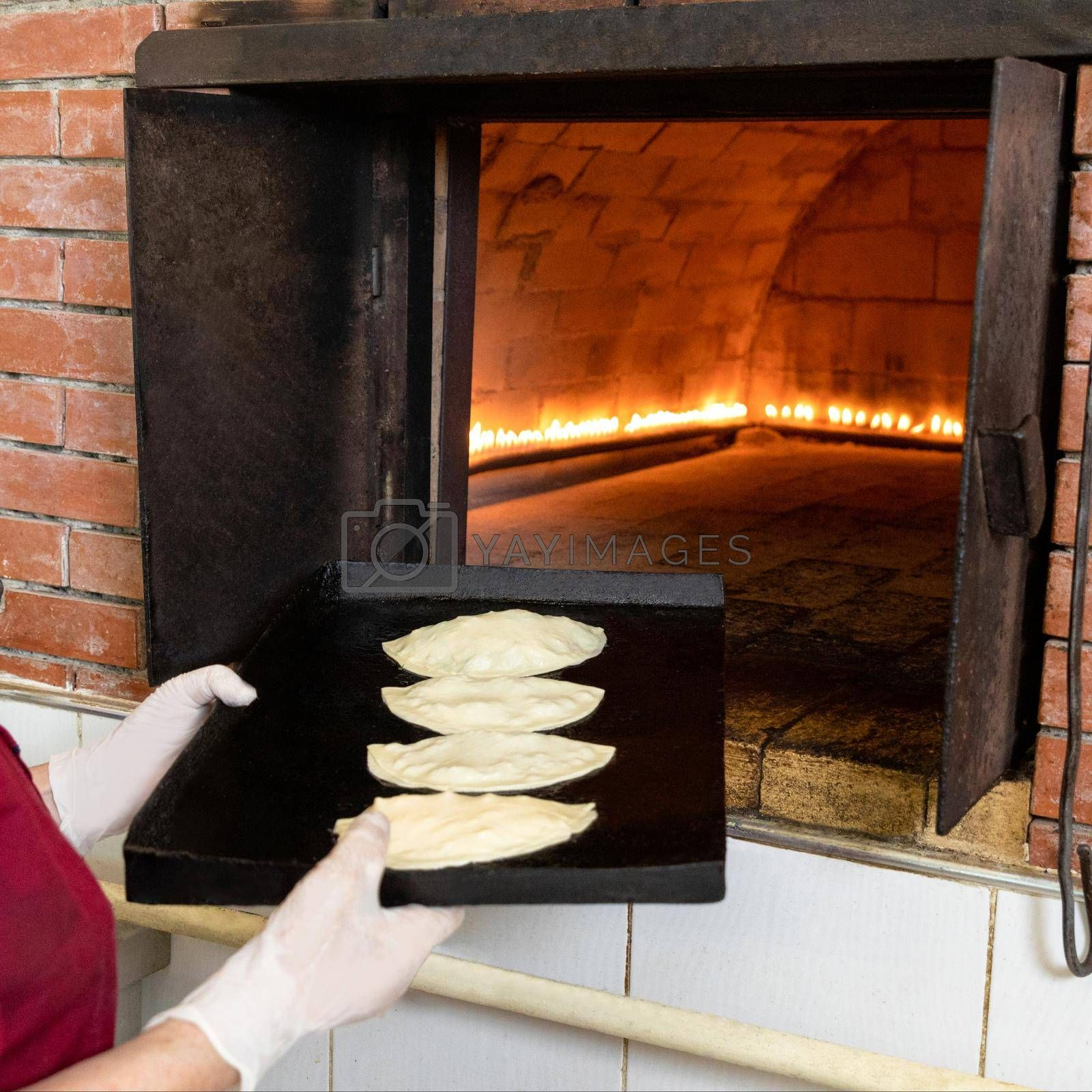 Woman putting qutab meal to the oven