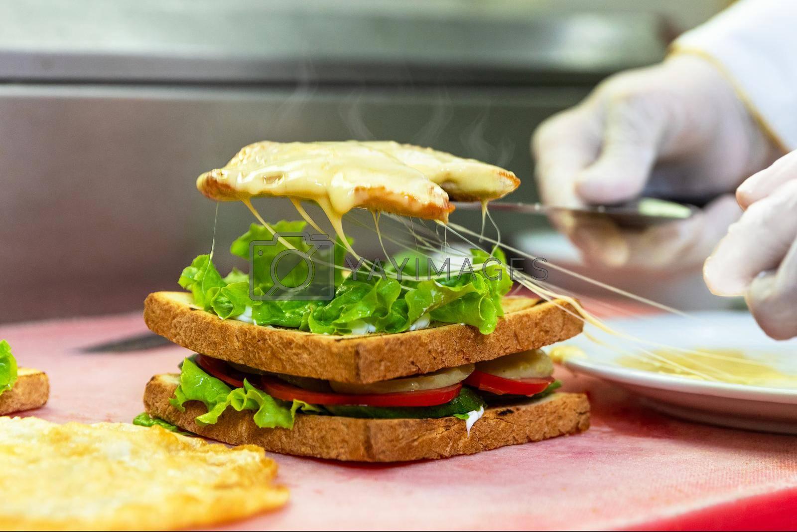Chef in restaurant kitchen making cheesy club sandwich