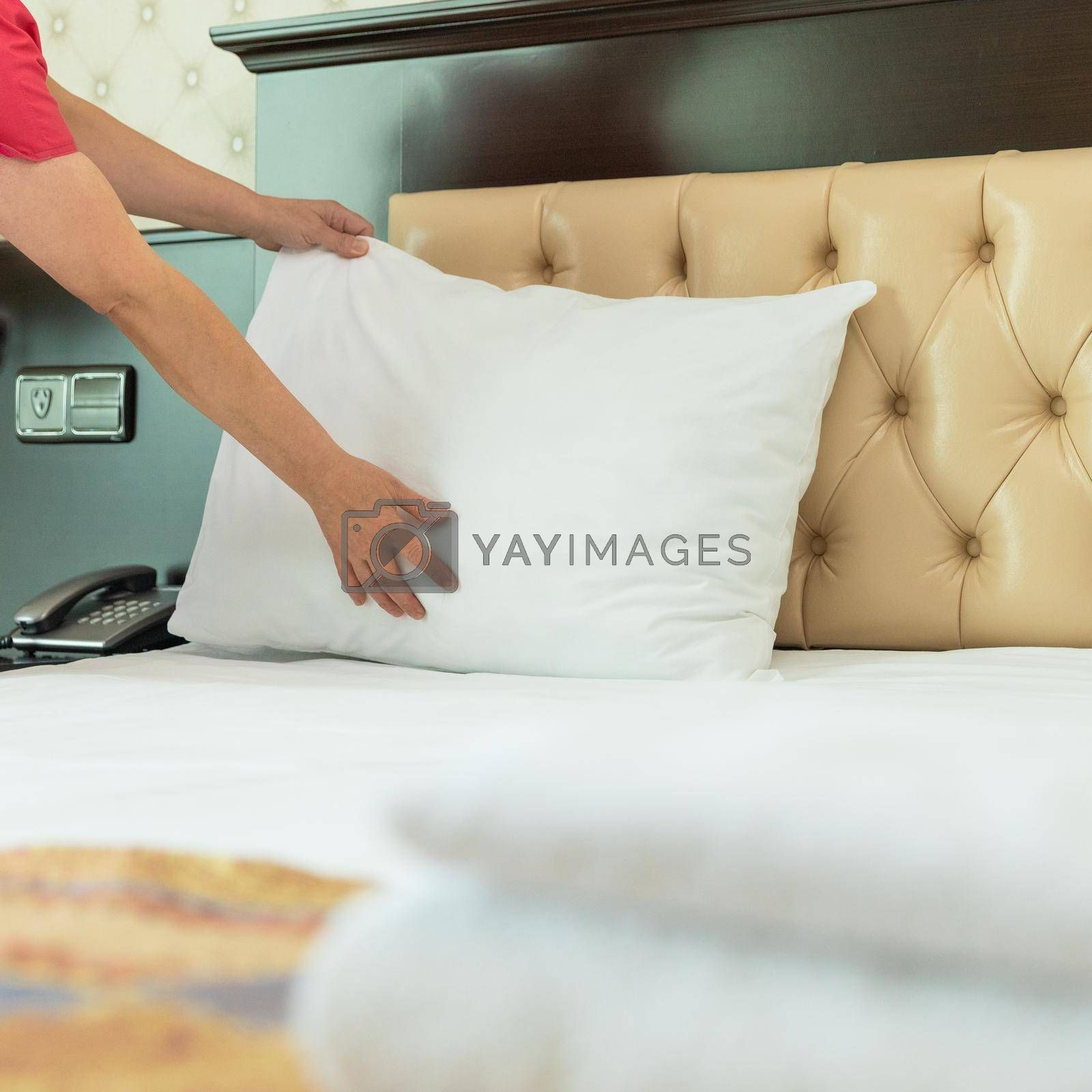 Hotel room service, woman making bed