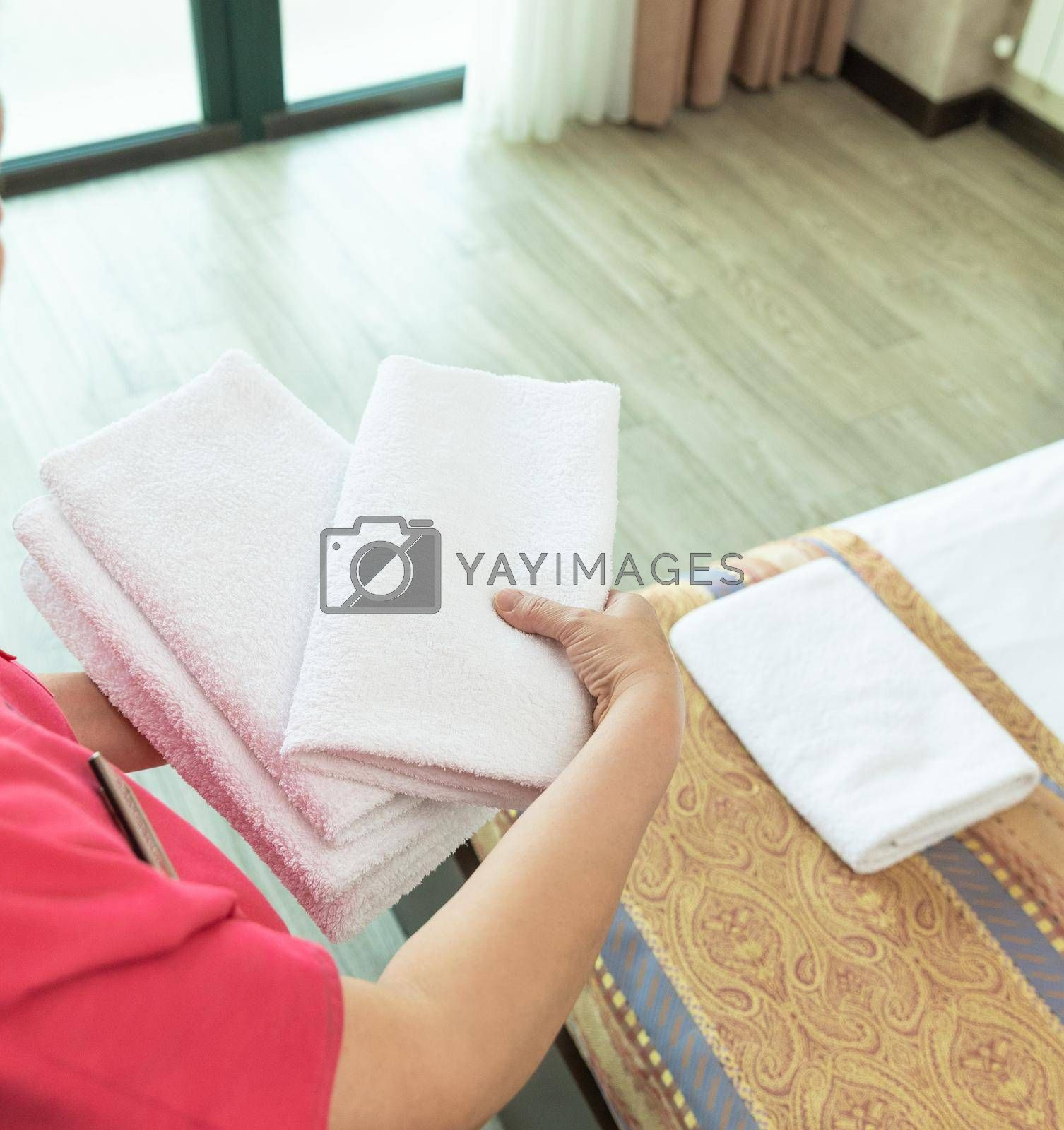 Hotel room service, woman puts a towel on the bed
