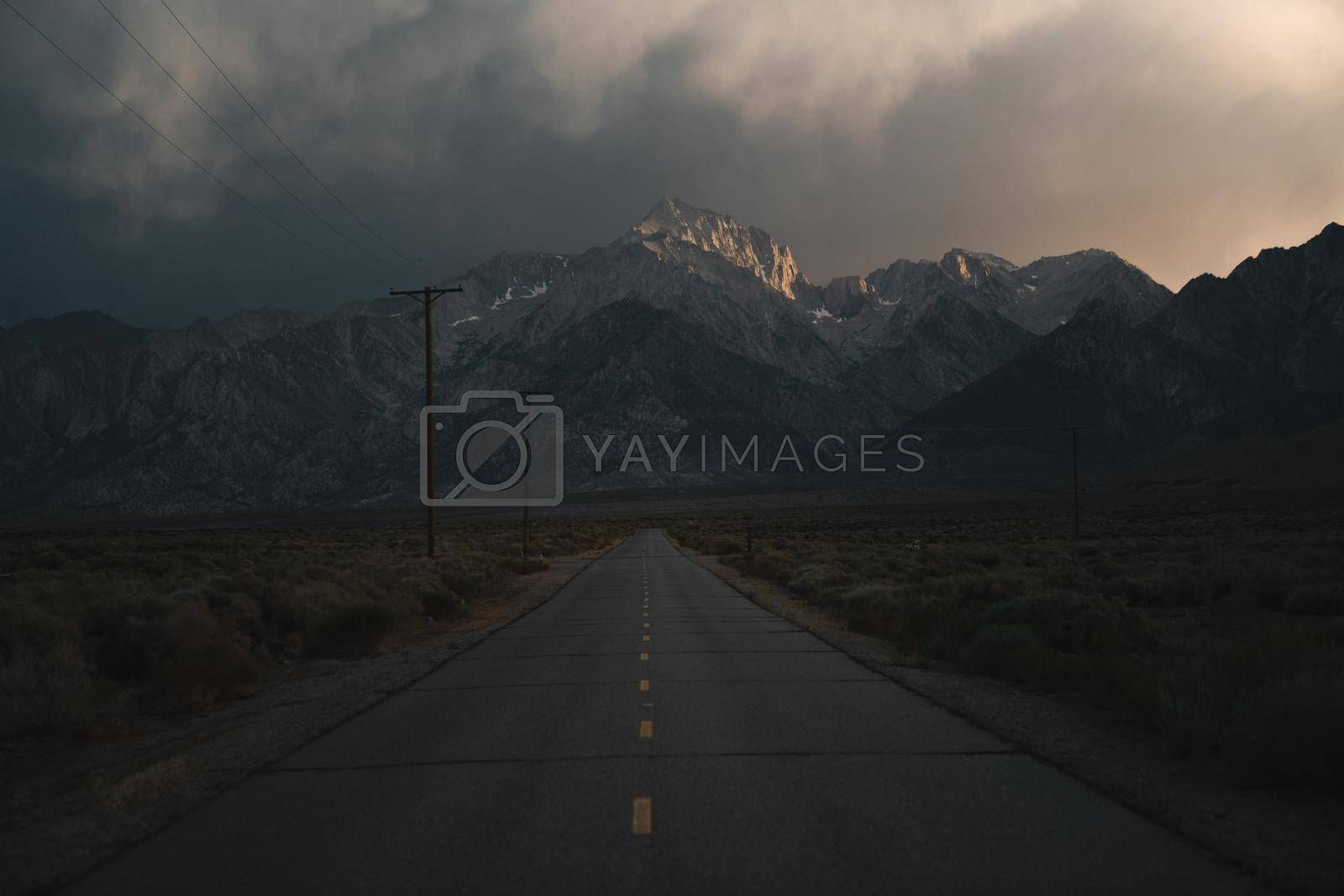 A dark, stormy road leading into the mountains.