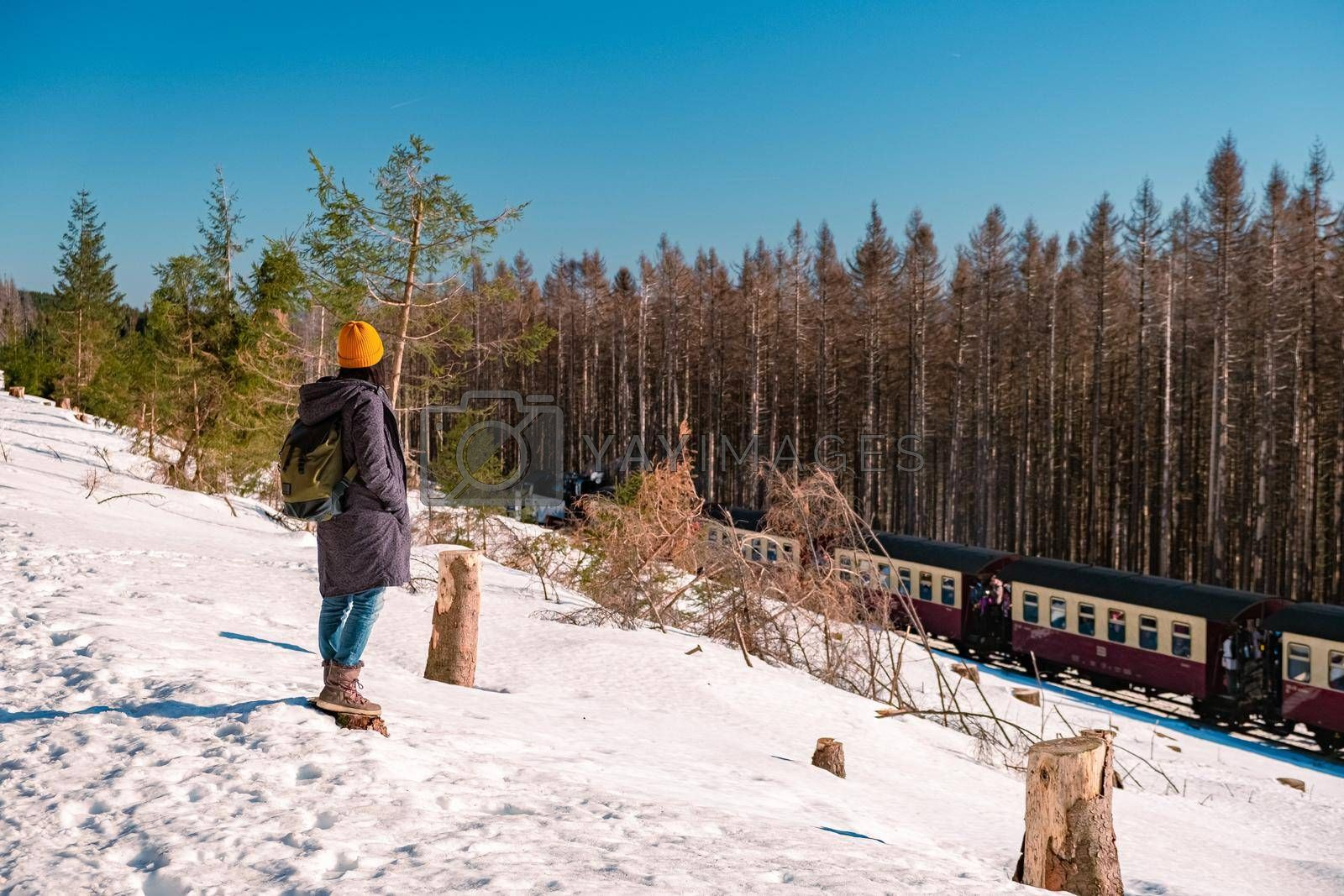 woman hiking in winter landscape Harz national park Germany, Steam train on the way to Brocken, Famous steam train through the winter mountain, Harz National Park Mountains in Germany Europe