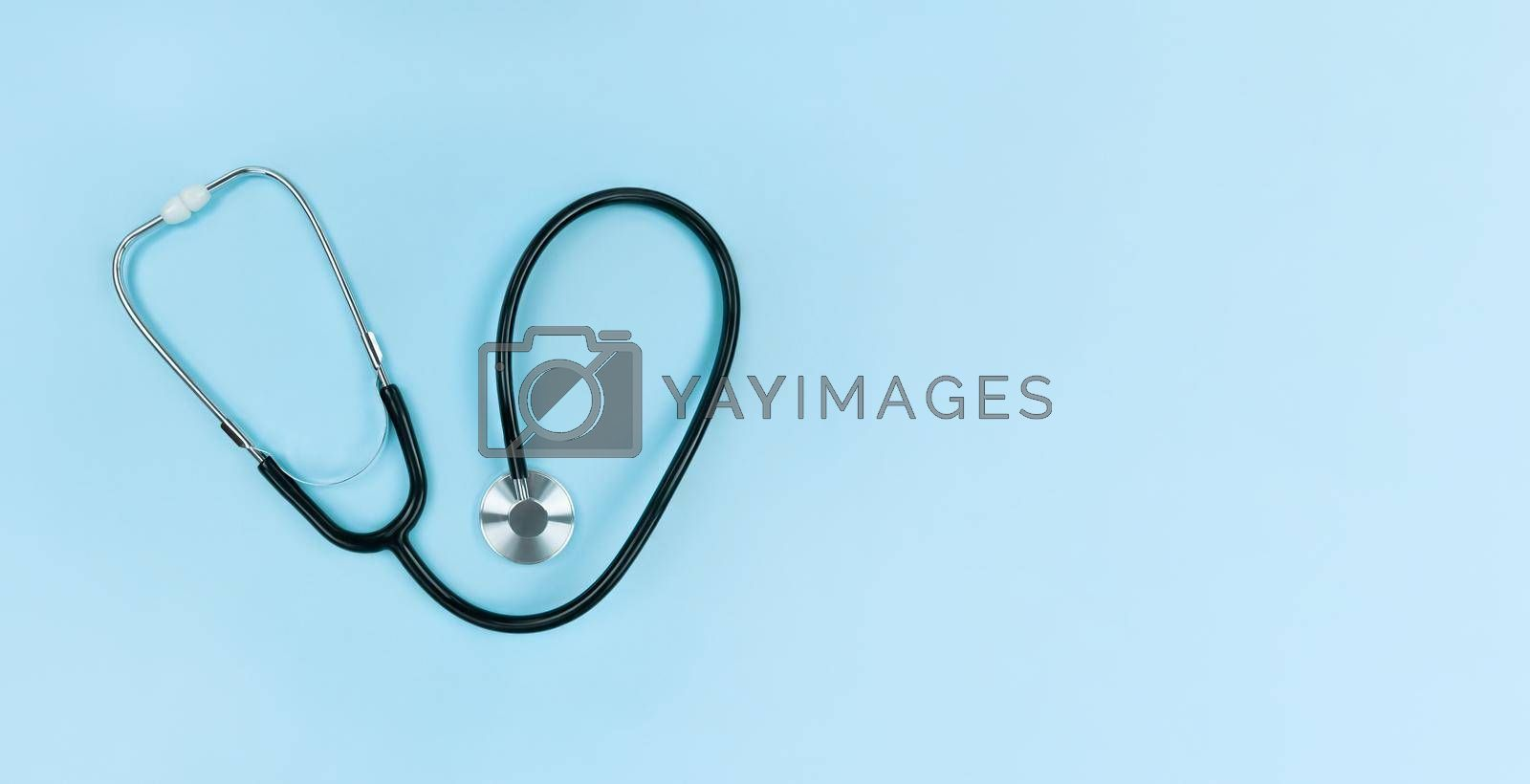 Black stethoscope on a soft blue background. Simple flat lay with copy space.