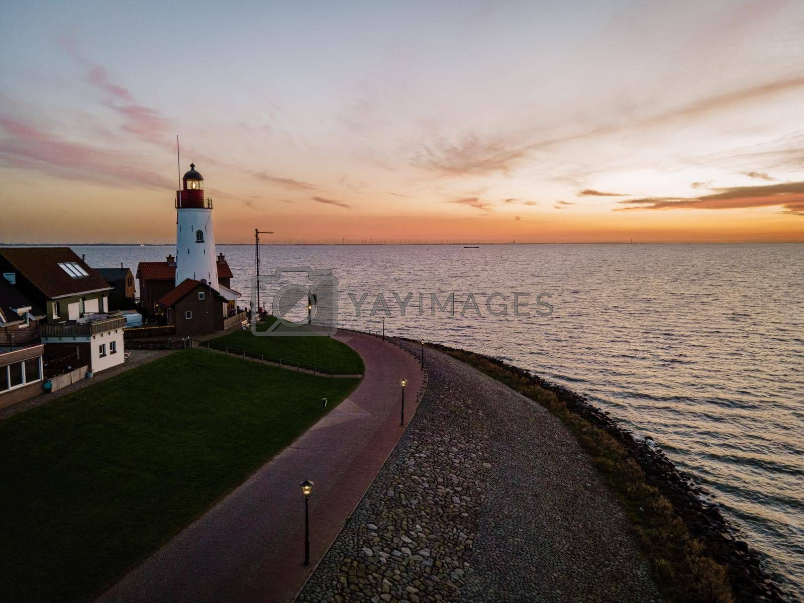 Urk lighthouse with old harbor during sunset, Urk is a small village by the lake Ijsselmeer in the Netherlands Flevoland area. beach and harbor of Urk