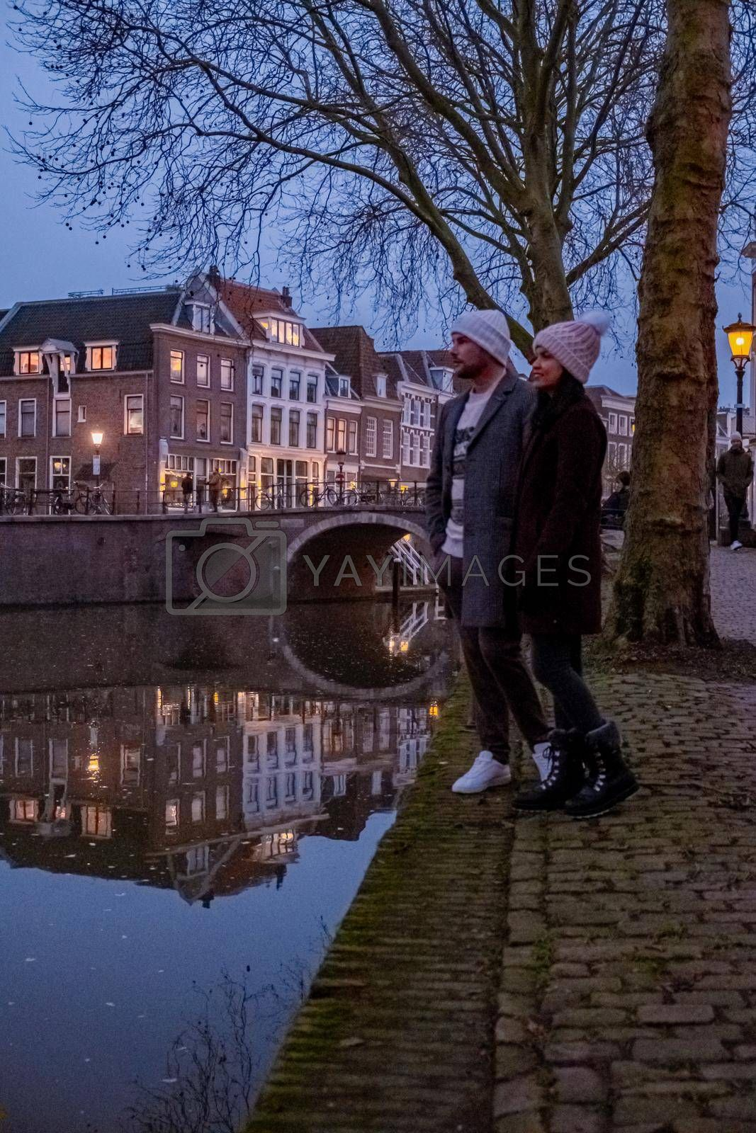 couple on a city trip in Utrecht, mid age Asian woman and European men visit Utrecht, Traditional houses on traditional houses on the Oudegracht Old Canal in the center of Utrecht, Netherlands Holland Europe
