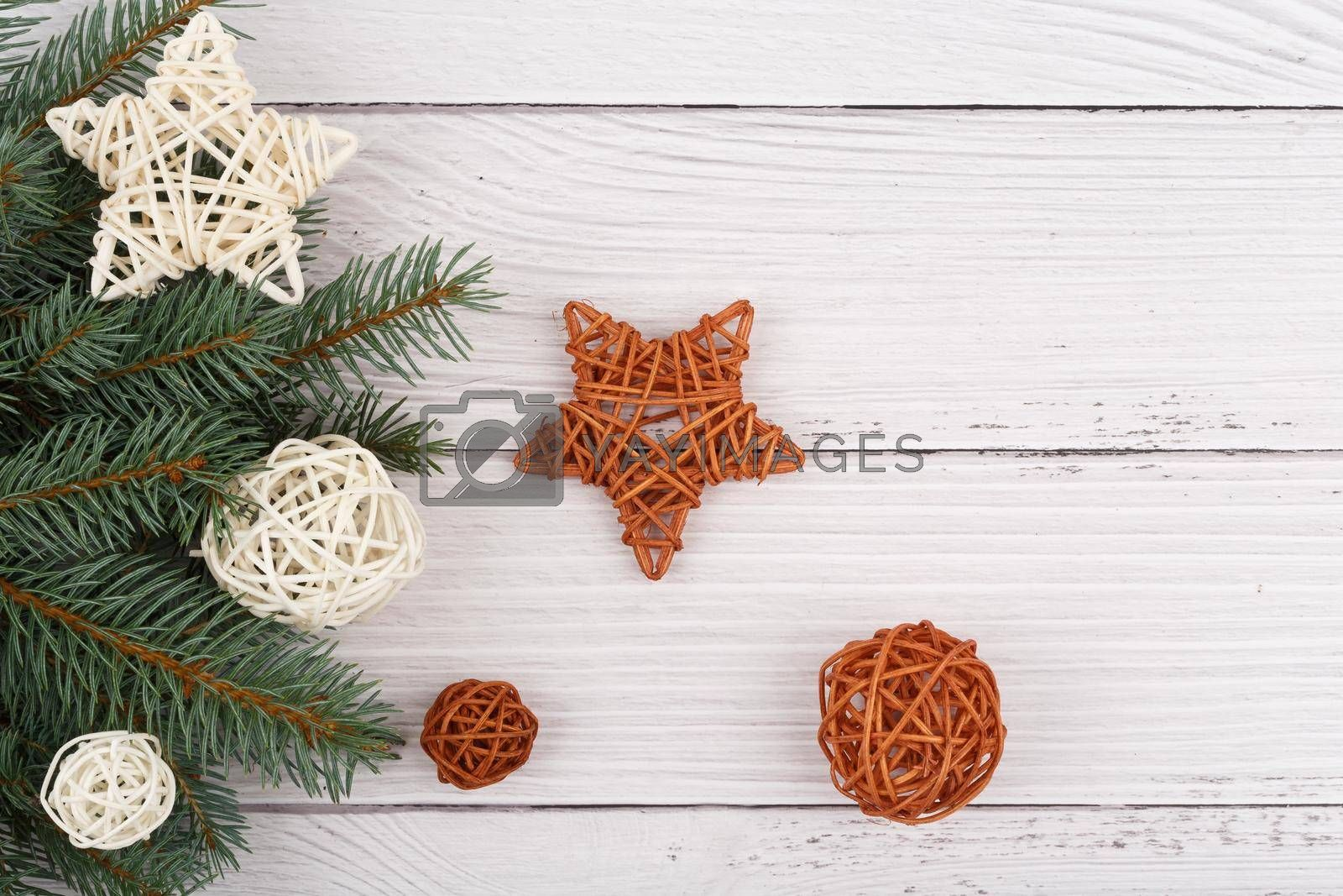 Top view of white rustic style wooden table decorated with white and brown rattan balls and stars. The concept of New Year and Christmas time