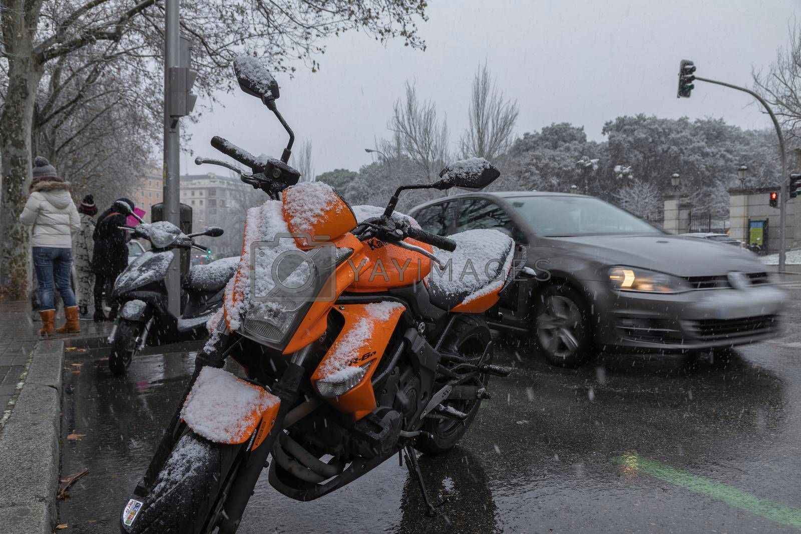 Orange motorbike, covered with snow, Madrid. by alvarobueno