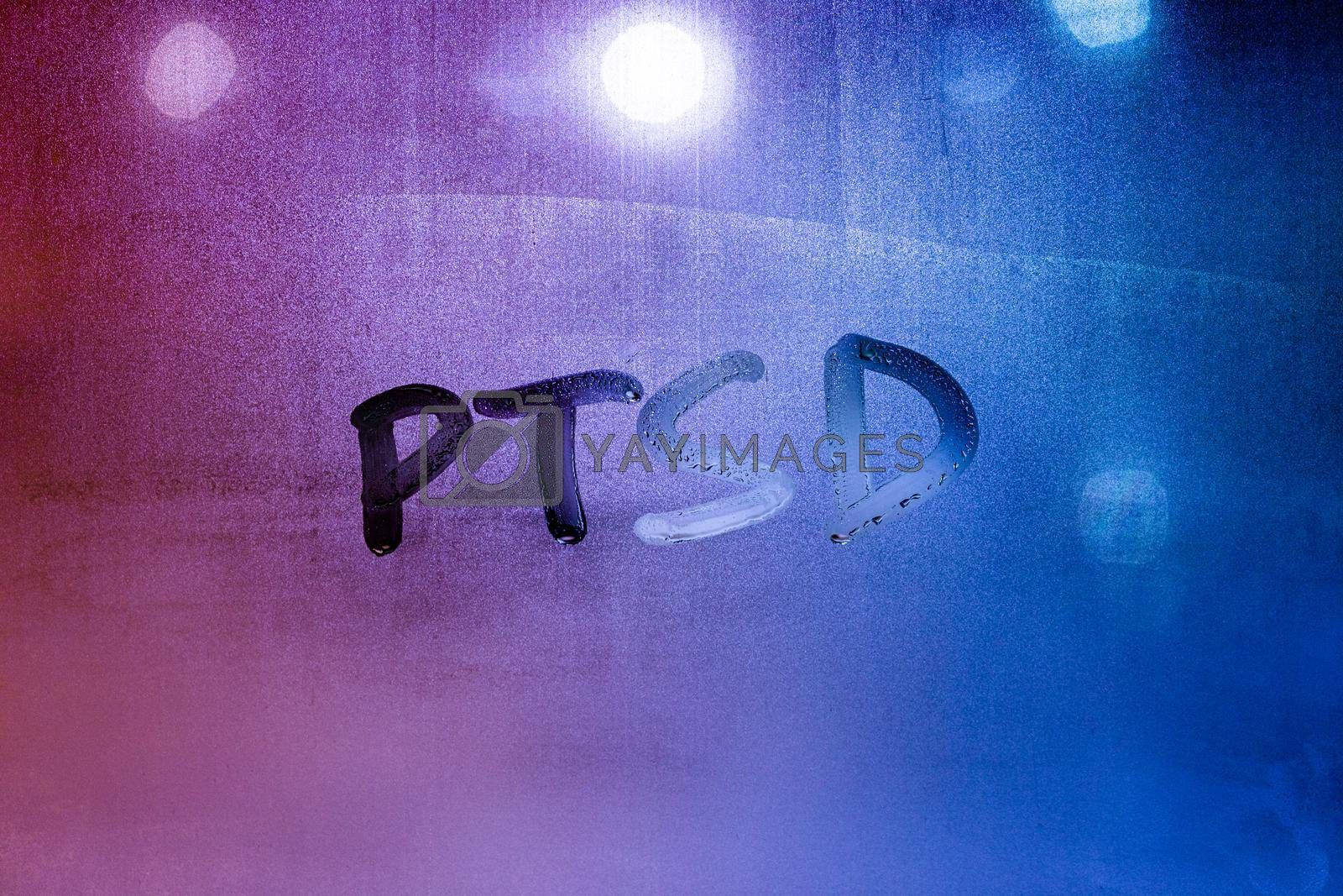 abbreviation ptsd - post traumatic stress disorder - handwritten on night wet window glass, close-up with selective focus