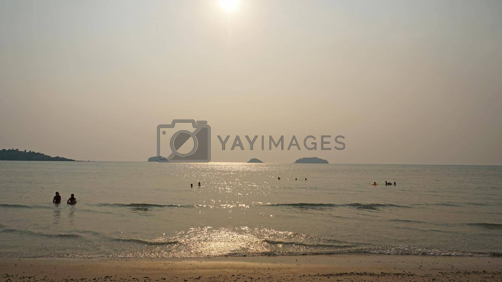 Smog obscures the sun's rays. People relax on the beach. Yellow rays of light. View of the islands, sand, sea and palm trees. Dirty air, smog. Chang Island, Thailand.