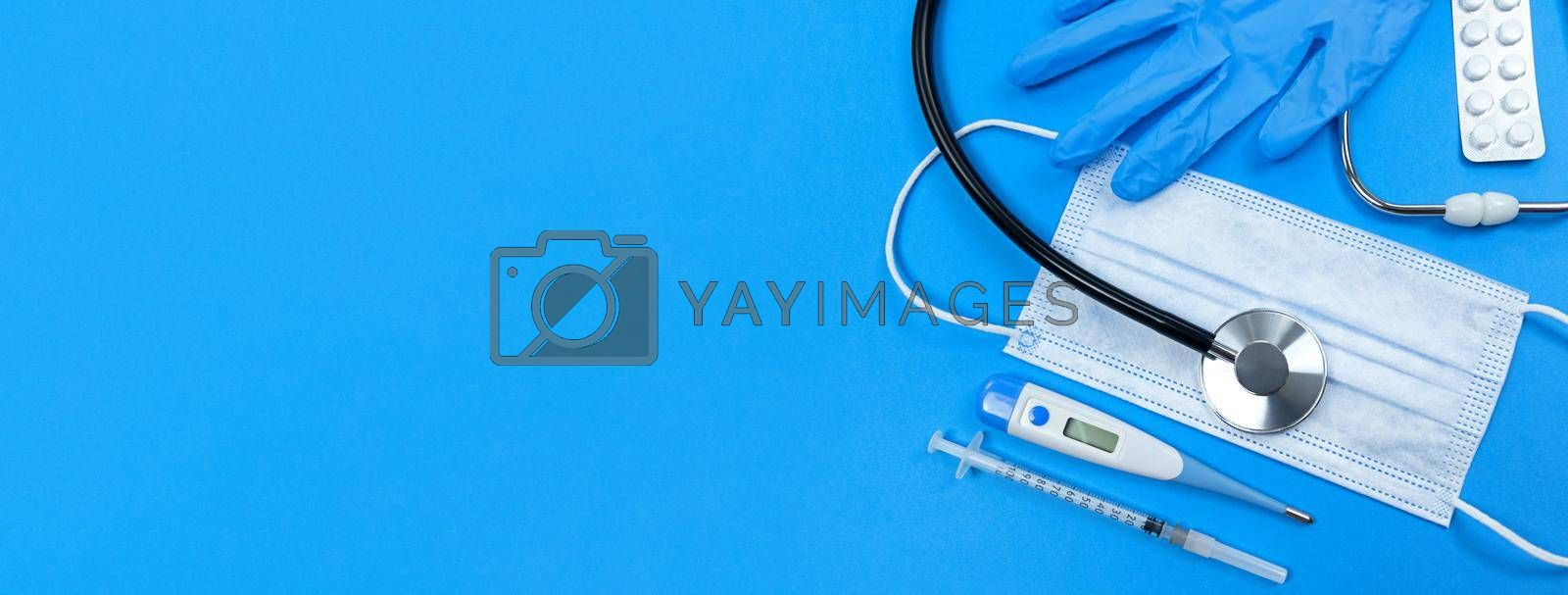 Stethoscope, face mask, medical syringe, thermometer, pills blister and medical gloves on a blue background. Flat lay banner with copy space.