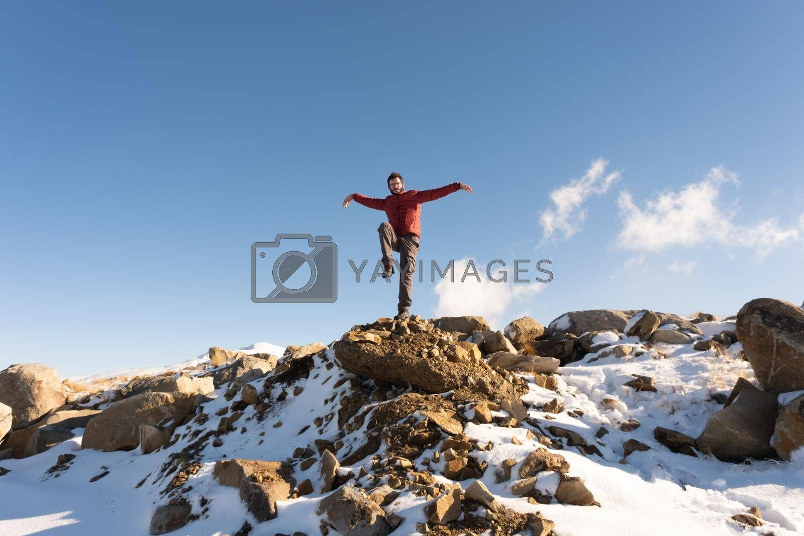 Motivated man making eagle movements on a rocky hill in a snowy mountain in Winter Long Shot with copy space achievement concept by OguzhanDursun