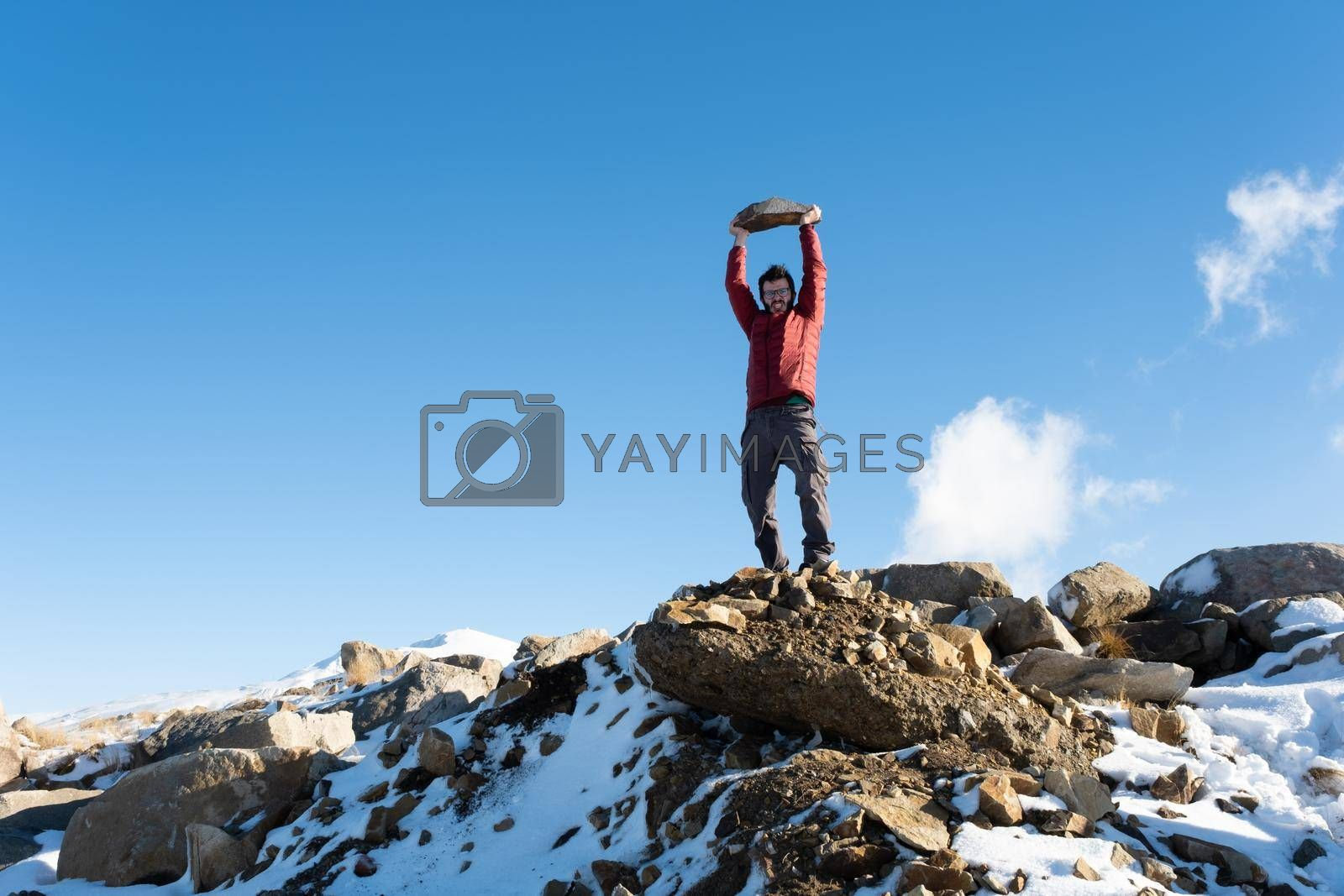It depicts a man with red jacket standing on the mountain and showing his success concept