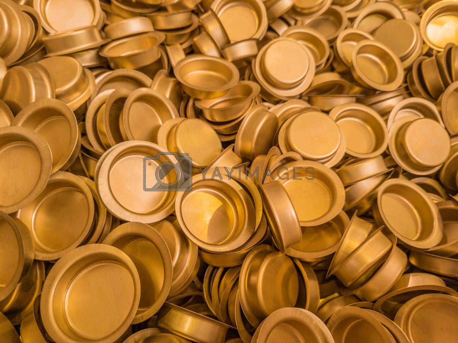 A pile of stamped thin sheet brass hat-shaped semimanufatures, full frame industrial manufacturing background. Closeup with selective focus and blur