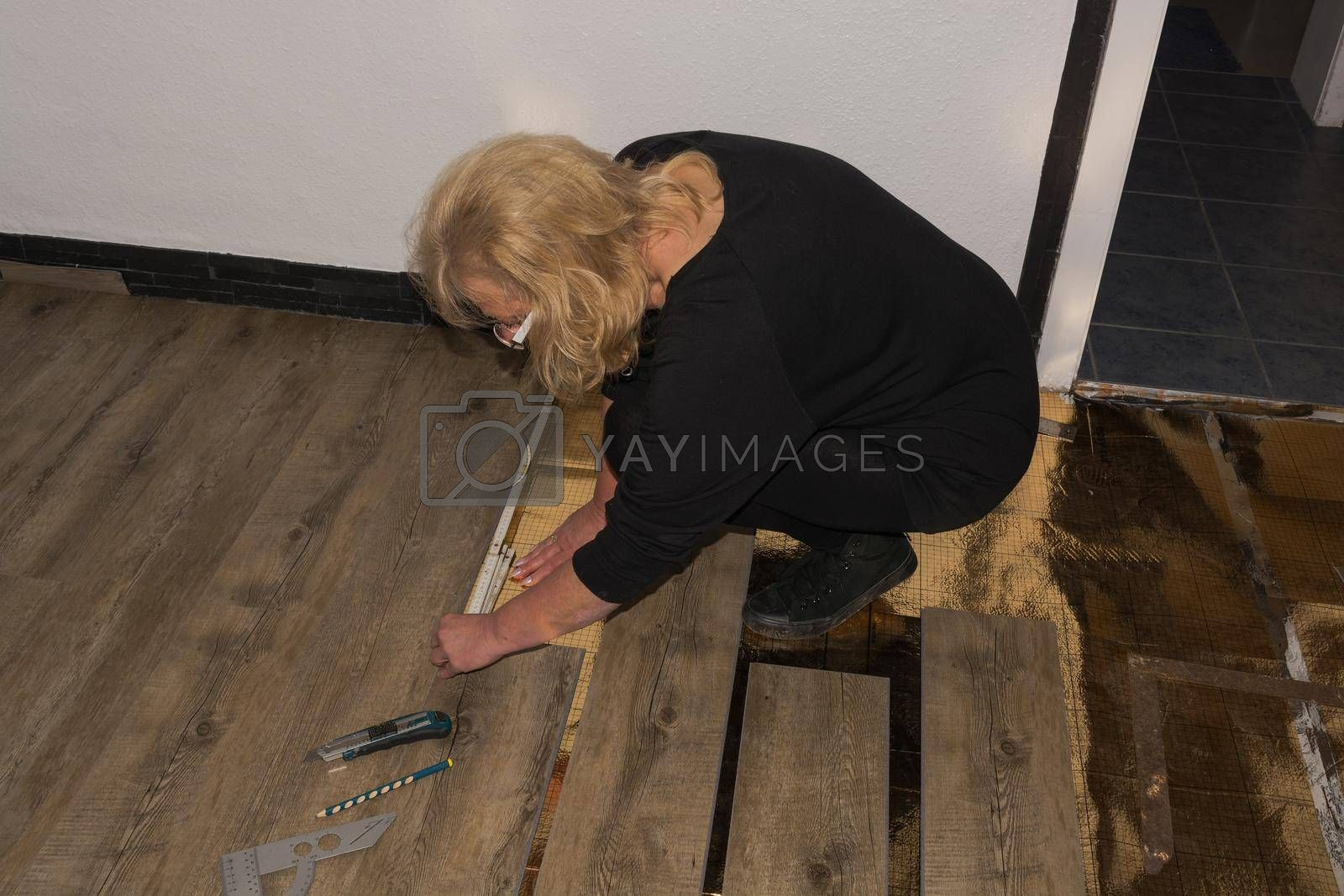 Royalty free image of Woman is laying laminate floor. repair concept by JFsPic