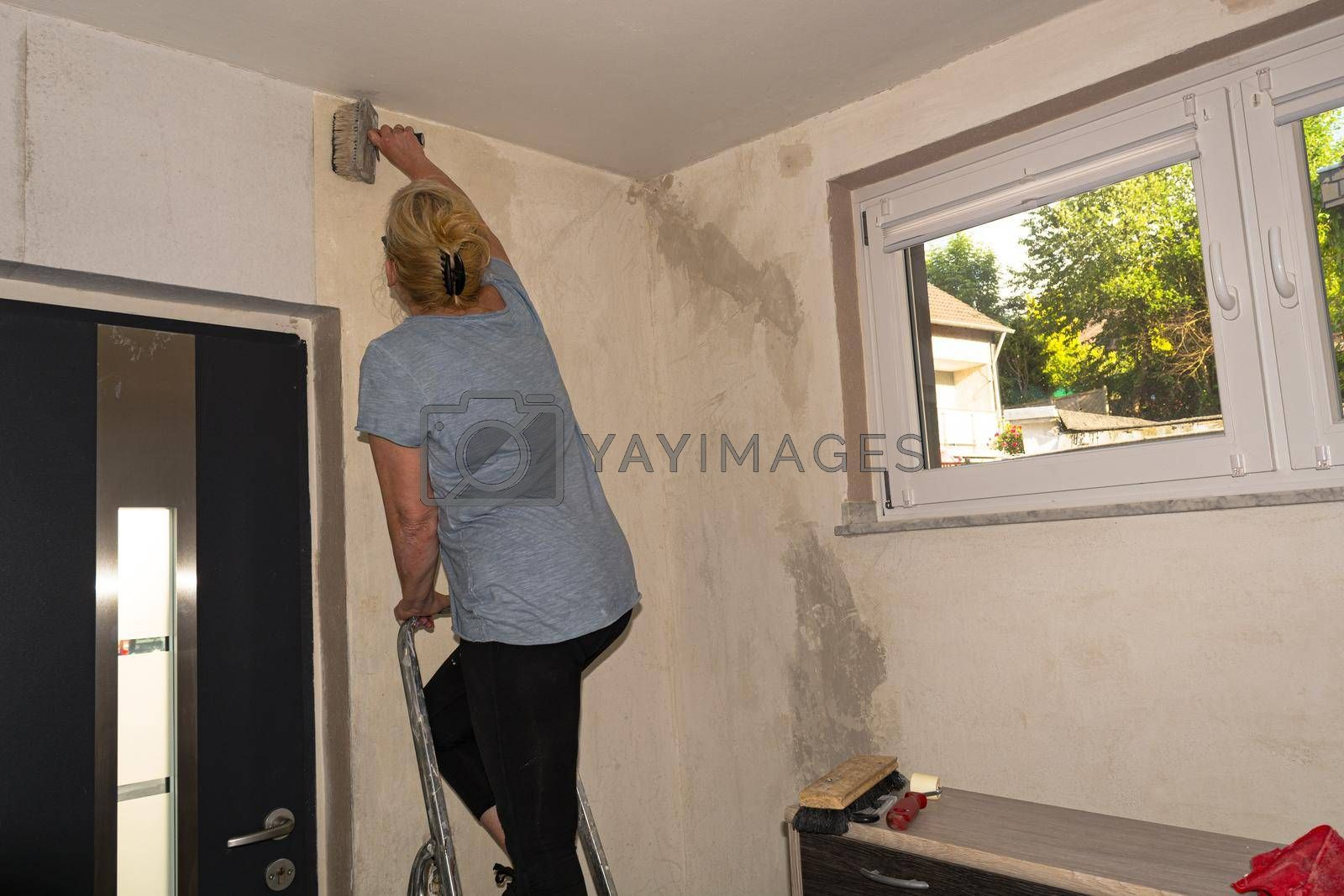 Royalty free image of Woman in casual clothes, rolls of wallpaper on a wall. by JFsPic