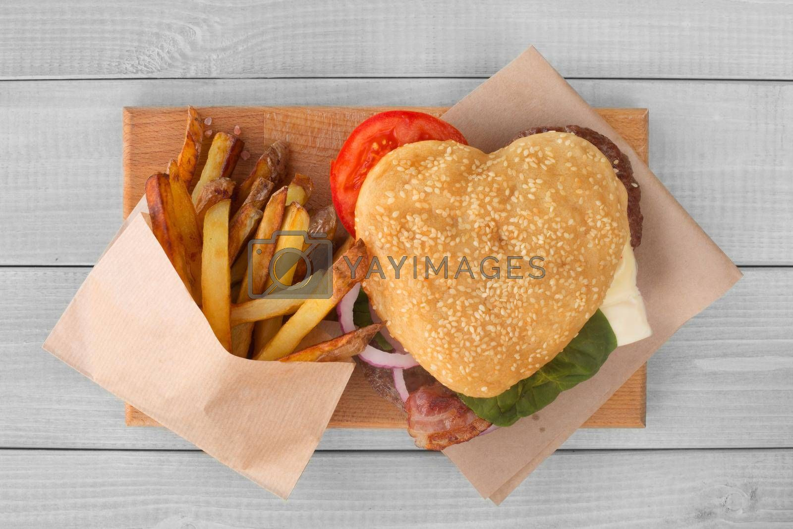 Heart shape love hamburger and french fries, burger fast food concept, Valentines day surprise dinner, wooden background, top view flat lay