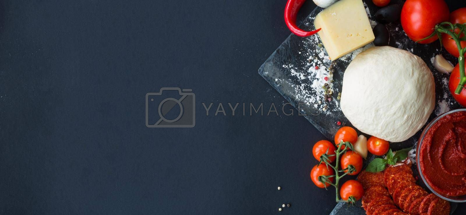 Raw dough for pizza with ingredients and spices on black table background with copy space for text