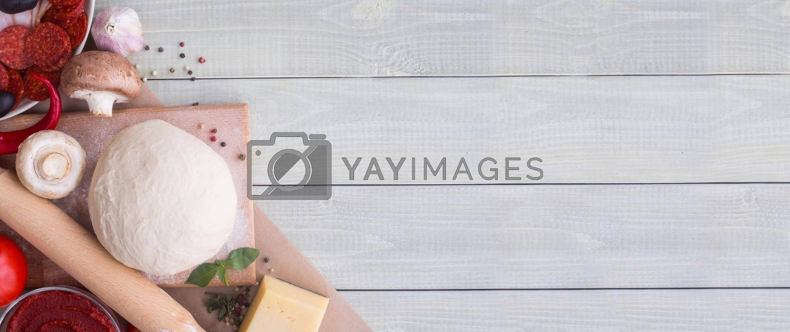 Raw dough for pizza with ingredients and spices on white wooden table background