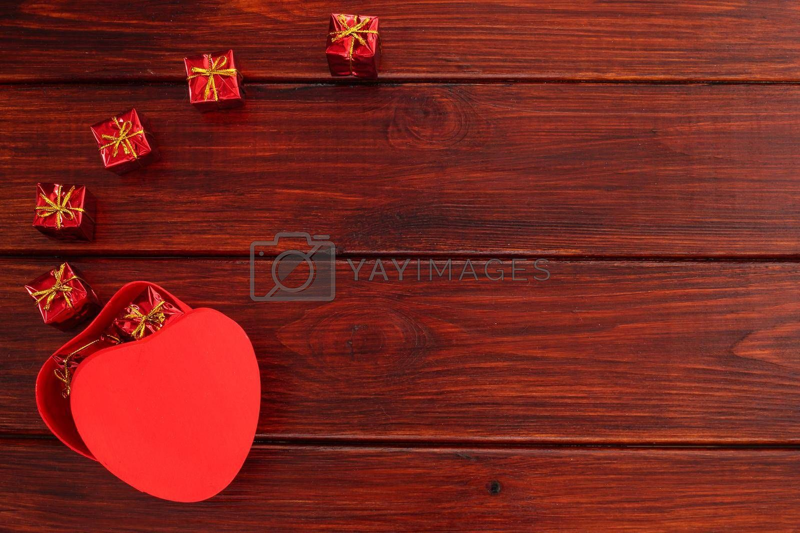 Heart shaped red box for valentines day gift on dark wooden table, top view