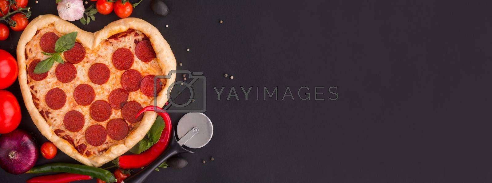 Pizza heart shaped with pepperoni with ingredients on black background. Concept of romantic love for Valentines Day . Love food, banner with copy space for text