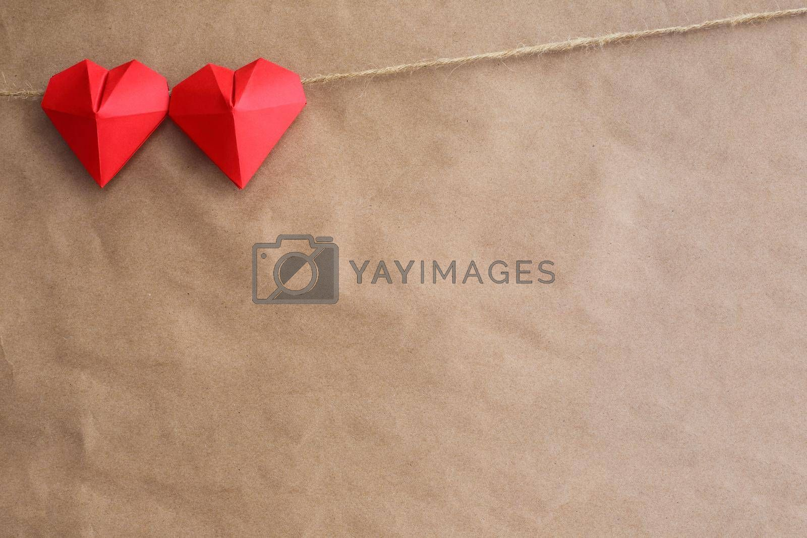 Red origami hearts on rope over paper background, Valentines day concept, copy space for text