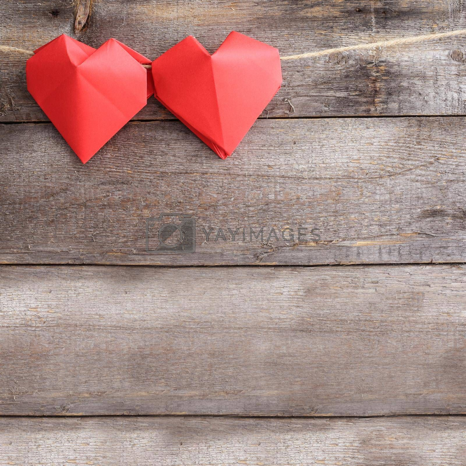 Red origami hearts on rope over wooden background, Valentines day concept, copy space for text