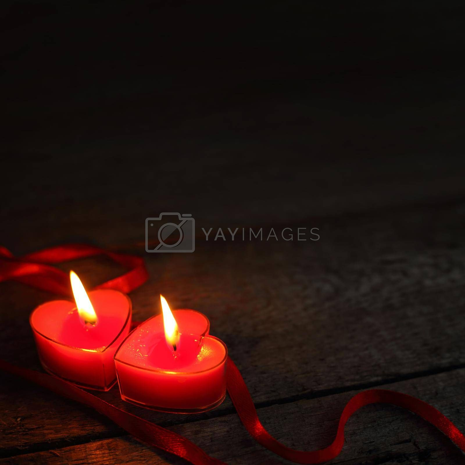 Heart shaped candles burning on wooden background, Valentines day concept
