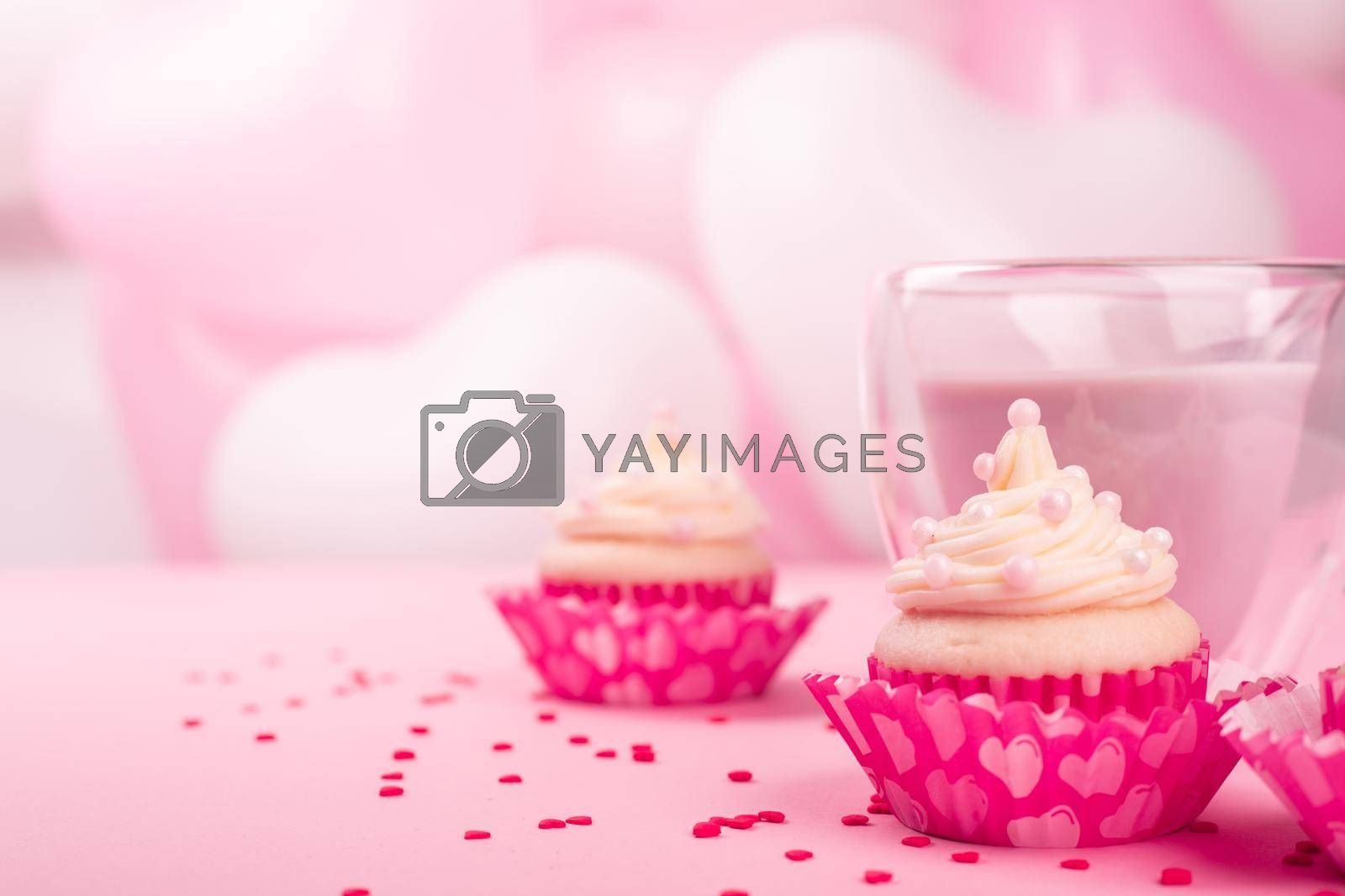 Valentine day love cupcake decorated with cream and hot chocolate on pink heart balloons background with copy space for text