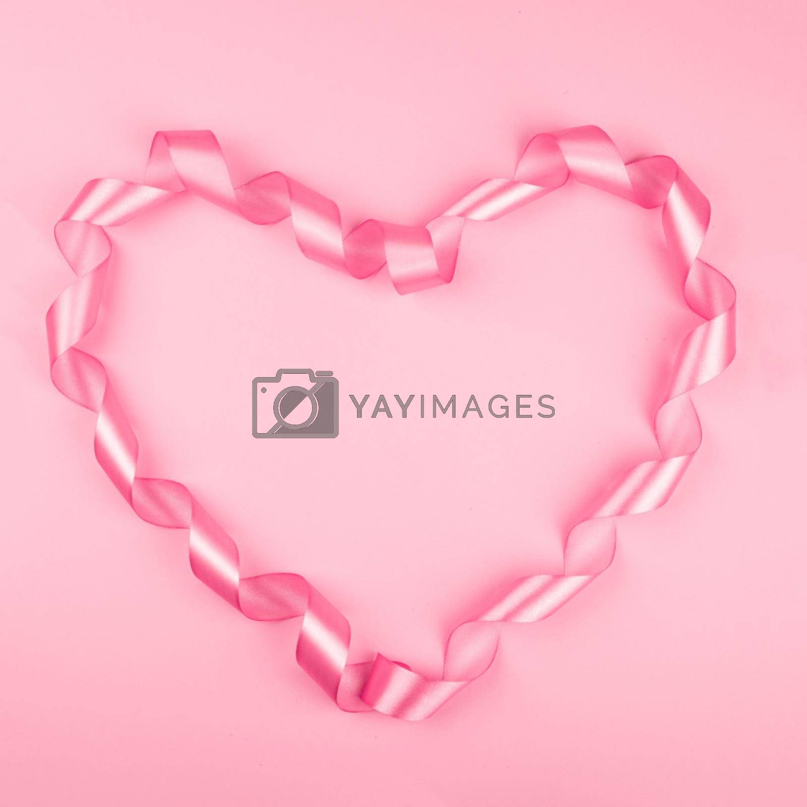 Valentine day background with pink curly satin ribbon in heart shape on paper on with copy space for text