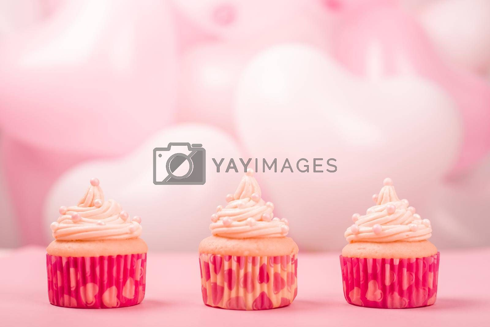 Valentine day love cupcakes decorated with cream and hearts on pink and white party balloons background with copy space for text