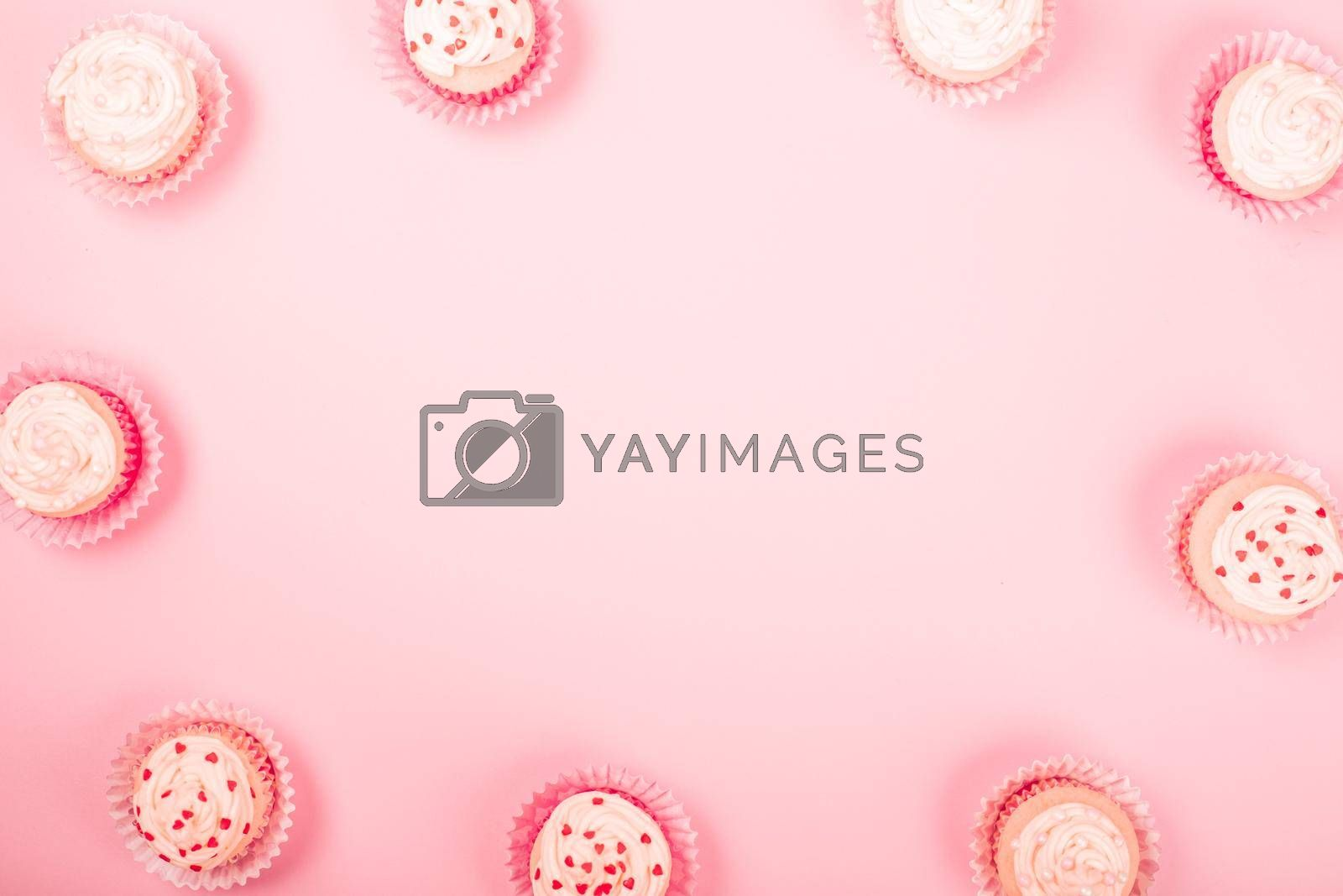 Valentine day love cupcakes decorated with cream and hearts on pink background border frame with copy space for text