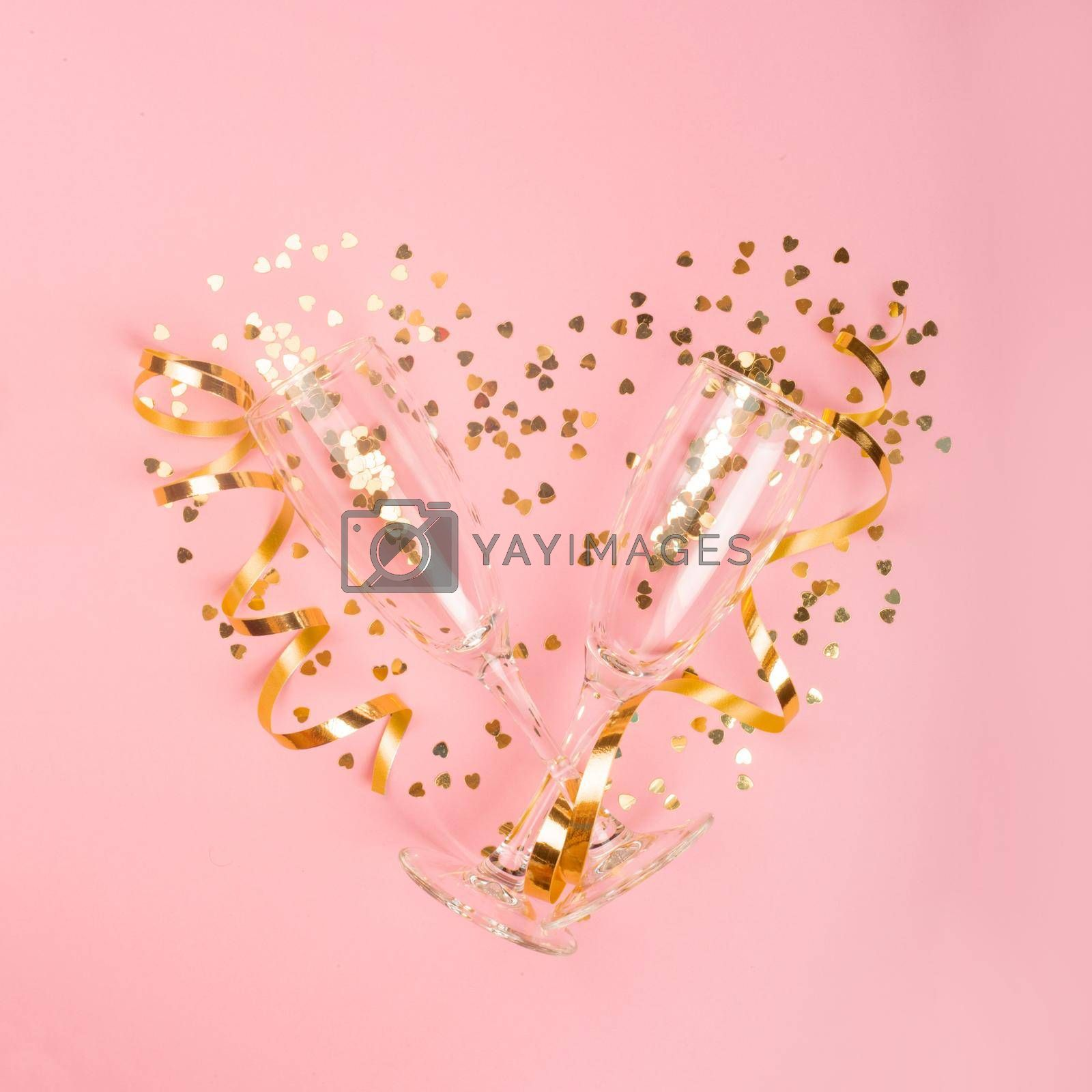 Valentines day champagne flutes glasses and heart shaped golden glitters on pink background with copy space for text