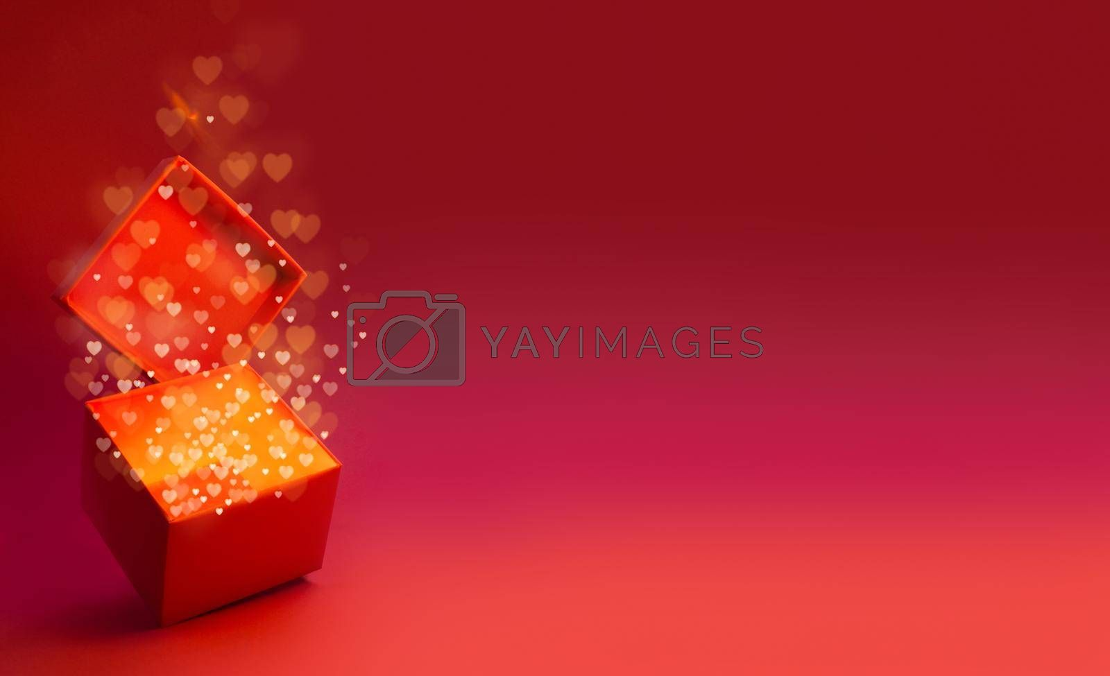 Magic box with love gift for Valentines day, pink red glowing with light from inside with bokeh hearts on glitter background with copy space for text