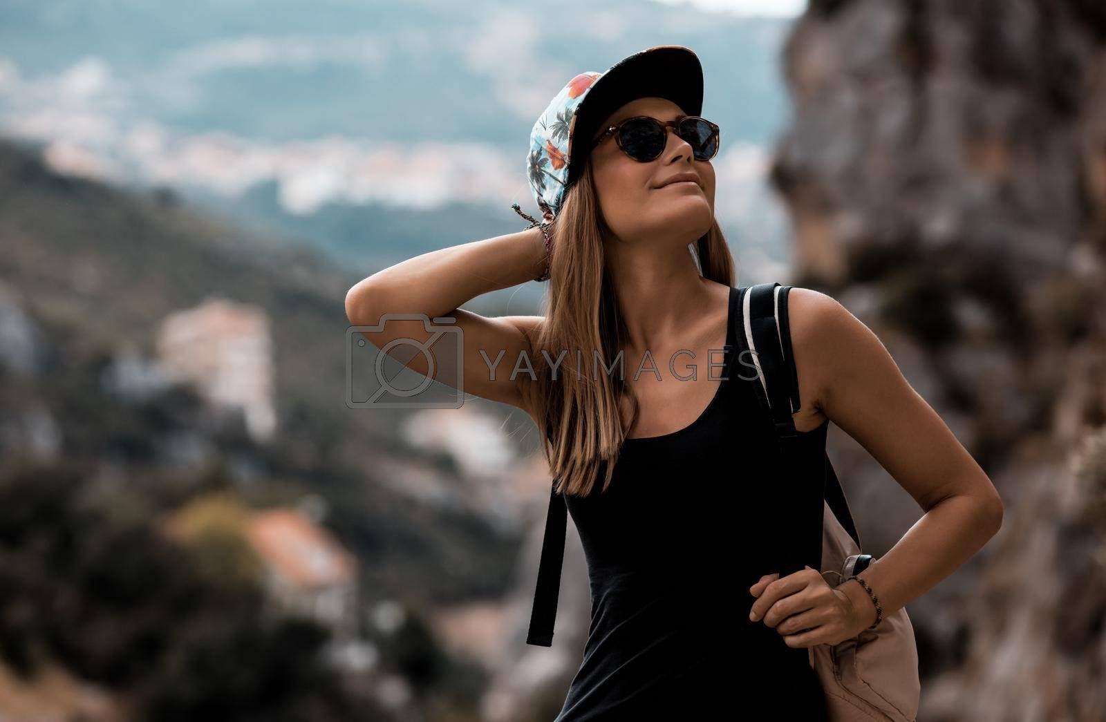 Portrait of a Nice Happy Girl With Backpack Trekking in the Mountains. Active Young Woman Enjoying Travel Among Beautiful Mountainous Nature.