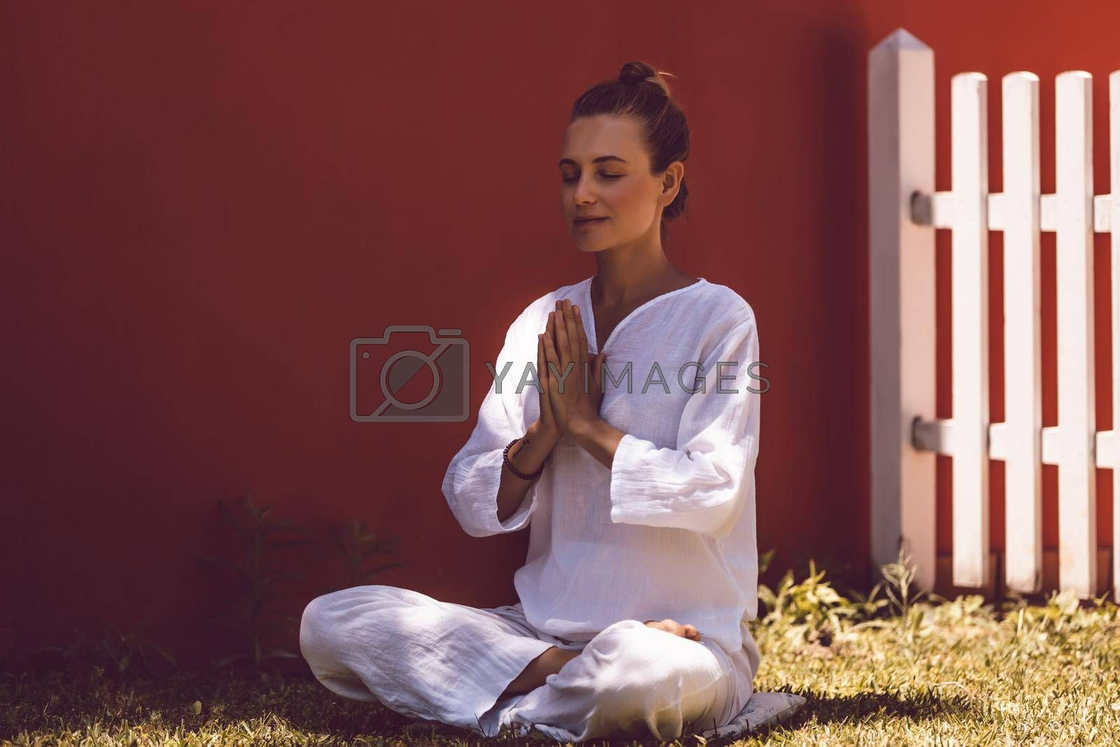 Beautiful Peaceful Female Doing Yoga Exercises in the Backyard. Meditates with Closed Eyes in Lotus Position. Healthy Lifestyle. Body Mind and Soul. Mindfulness Concept