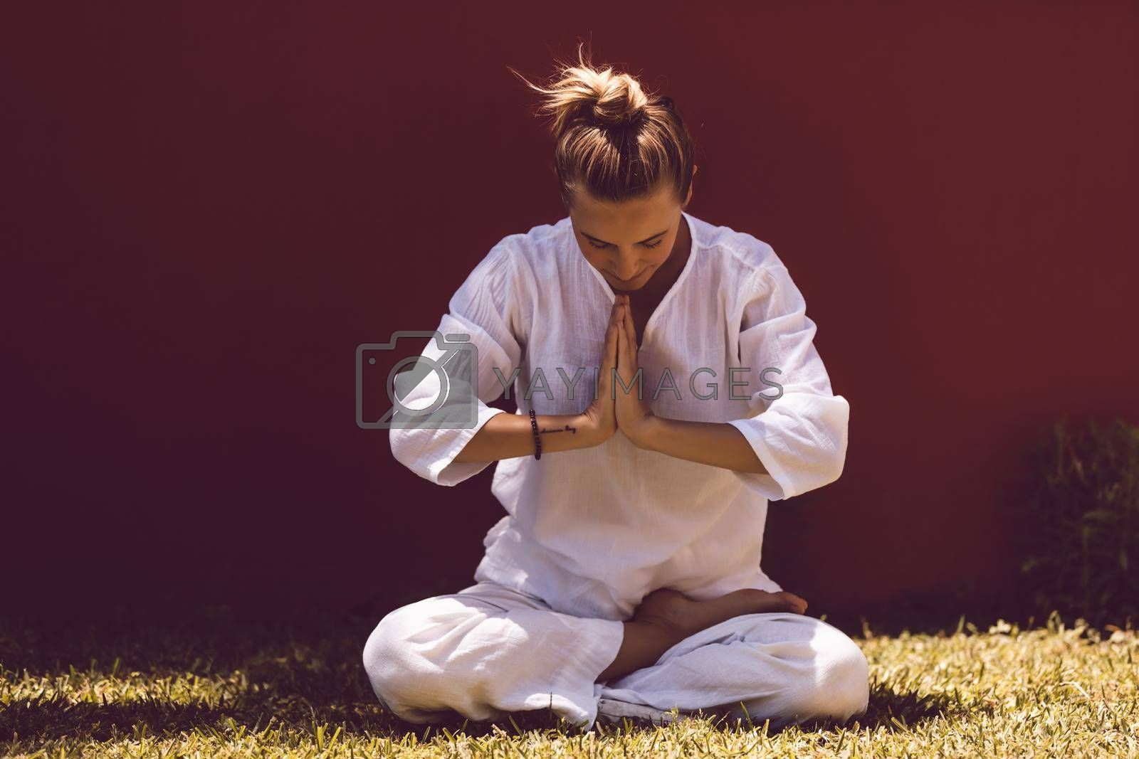 Pretty Woman Dressed in Clean White Clothes Sitting in Lotus Posture. Meditation Outdoors. Body Care and Mental Health. Namaste