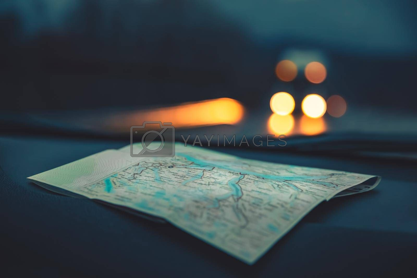 Close Up Photo on a Map used in the Car. Automobile Lights on the Highway at Night. Traveling Concept