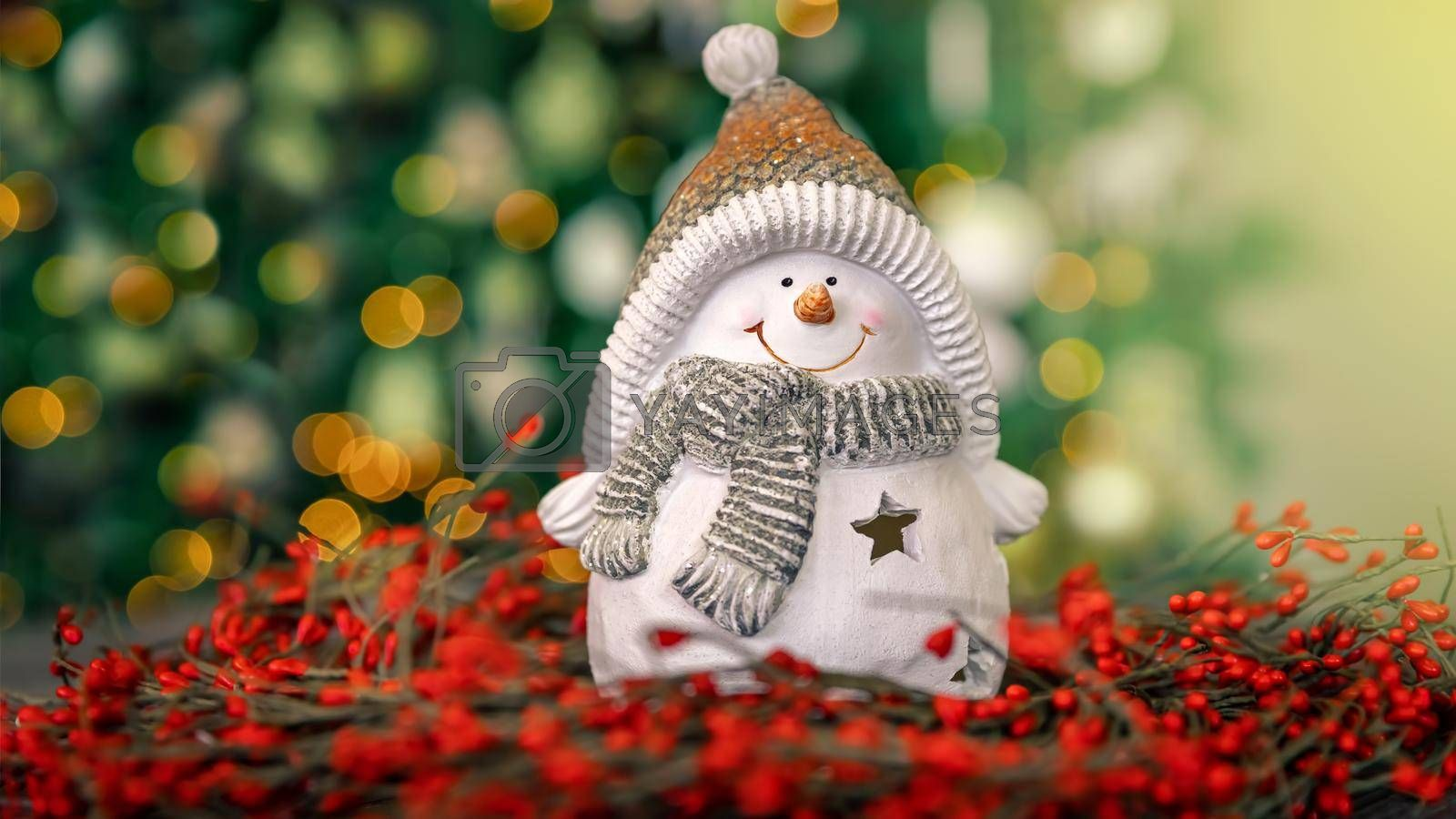 Nice Little Snowman Candlestick on the Table over Decorated Glowing Christmas Tree Bokeh Lights Background. Happy Winter Holidays at Home. Merry Christmas and Happy New Year