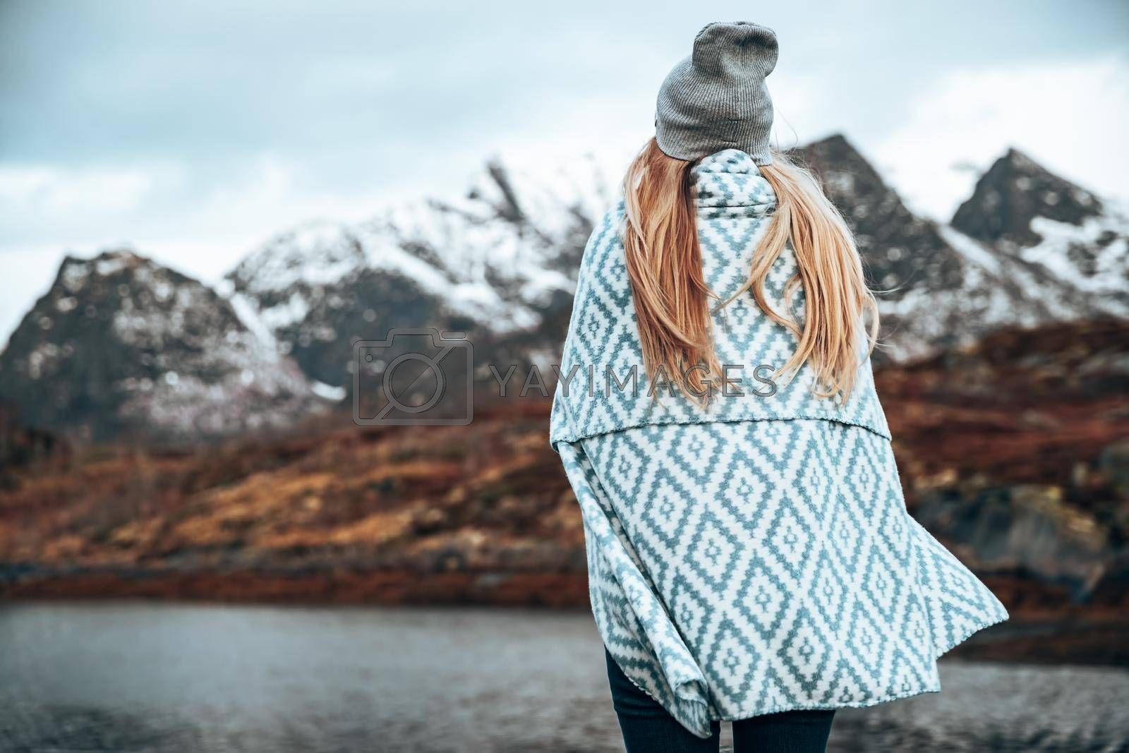 Back Side View of Female Wrapped in Blanket Enjoying Beautiful Landscape of a Majestic Mountains. Amazing Nature of Lofoten Islands. Norway