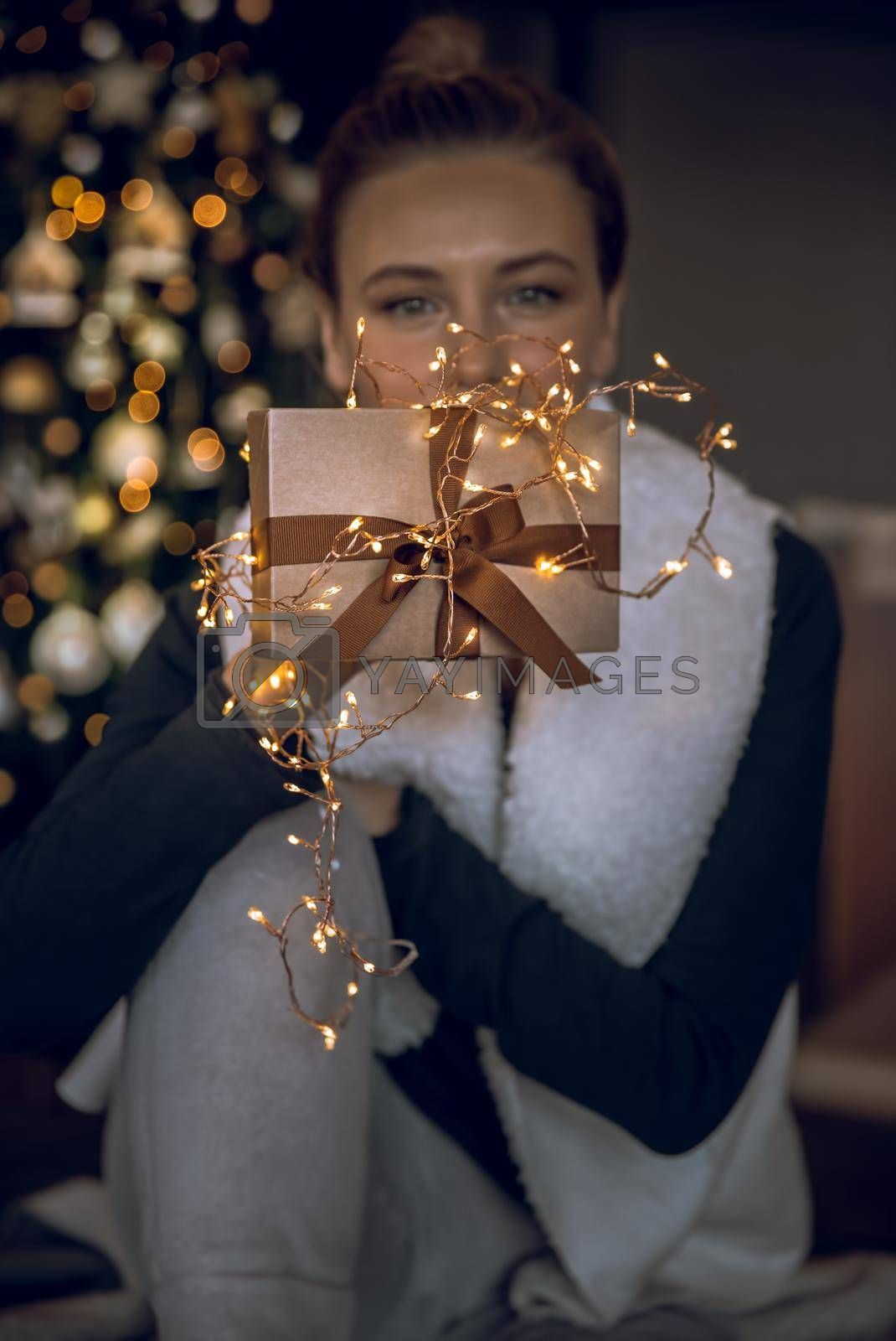 Pretty Girl with Pleasure Receiving Festive Gift. Stylish Golden Gift Box Decorated with Glowing Garland Light. Hygge Christmas Mood at Home. Preparing and Celebrating Winter Holidays. Merry Christmas and Happy New Year