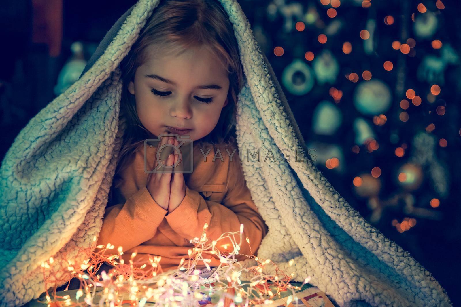 Kid Making Magic Wish for Winter Holidays. Baby Near the Christmas Tree at Home. Under the Plaid Praying. Waiting for Santa at Night.