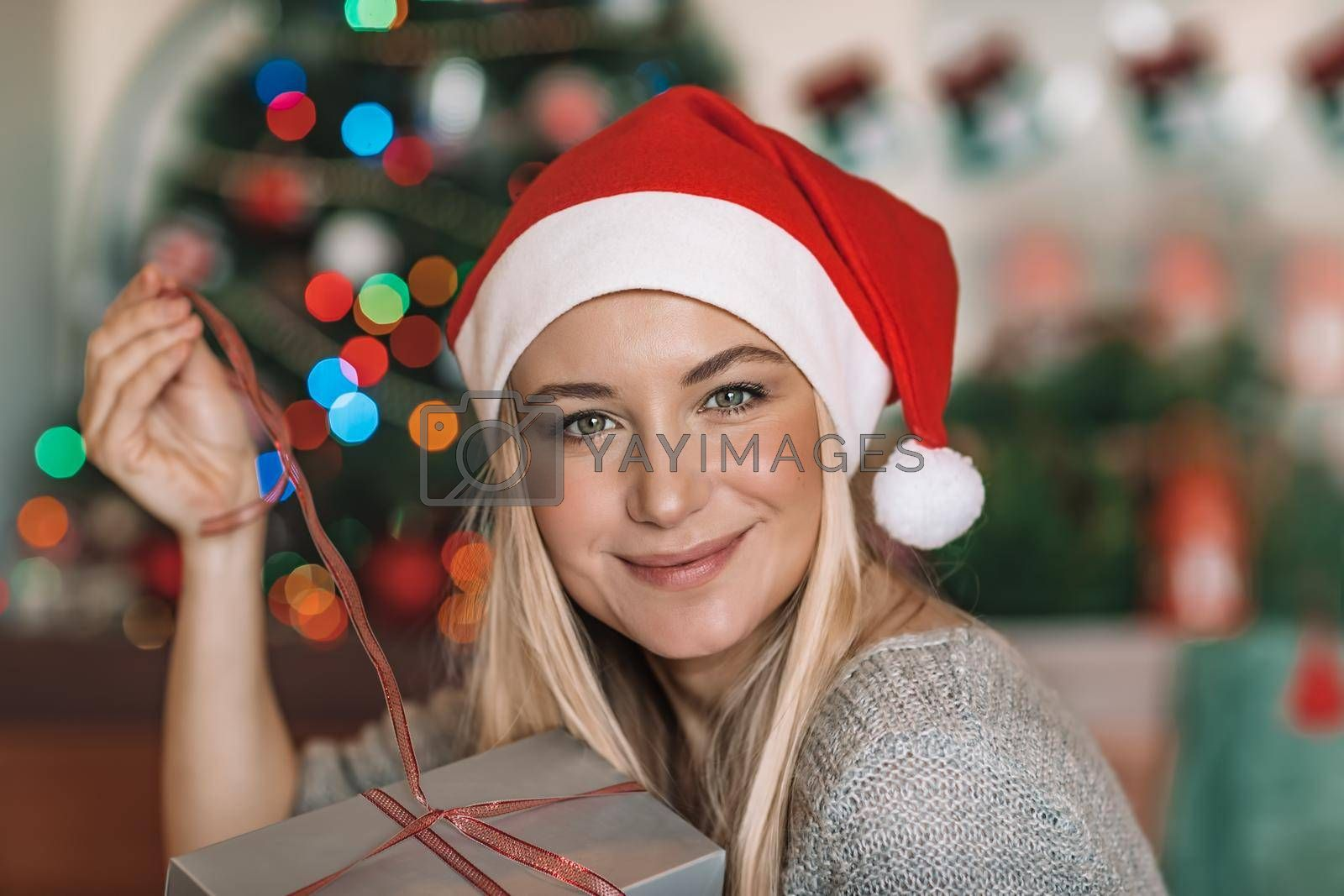 Portrait of a Cheerful Blond Female Wearing Red Santa Hat with Gift Box near the Christmas Tree. Happy Santa Helper. Cozy Christmas Eve at Home.