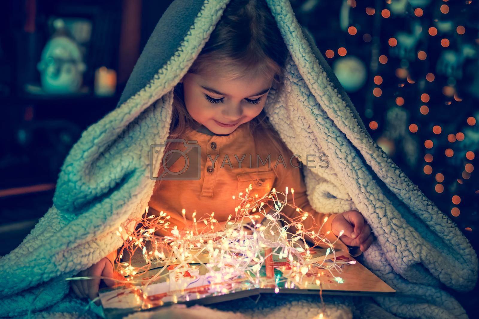 Cute Little Baby Reading Magic Christmas Tale. Kid Enjoying Beautiful Cozy Christmas Eve at Home. Hygge Mood.