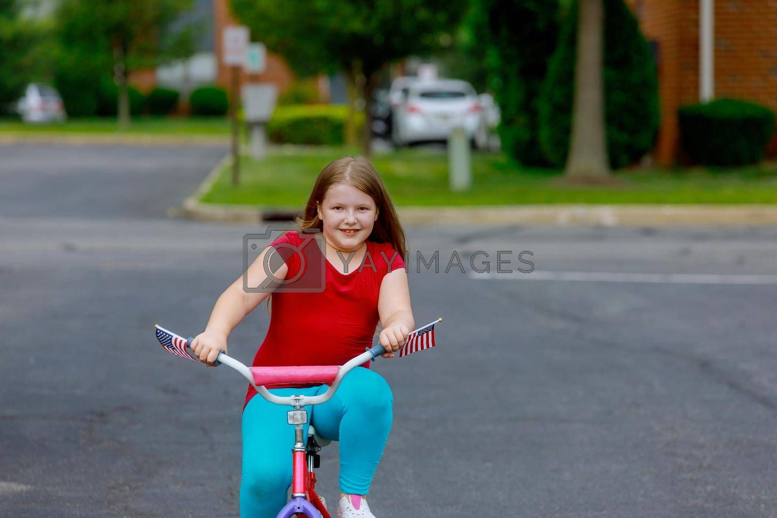 Smiling little girl in the summer clothes riding bicycle at the park on a city