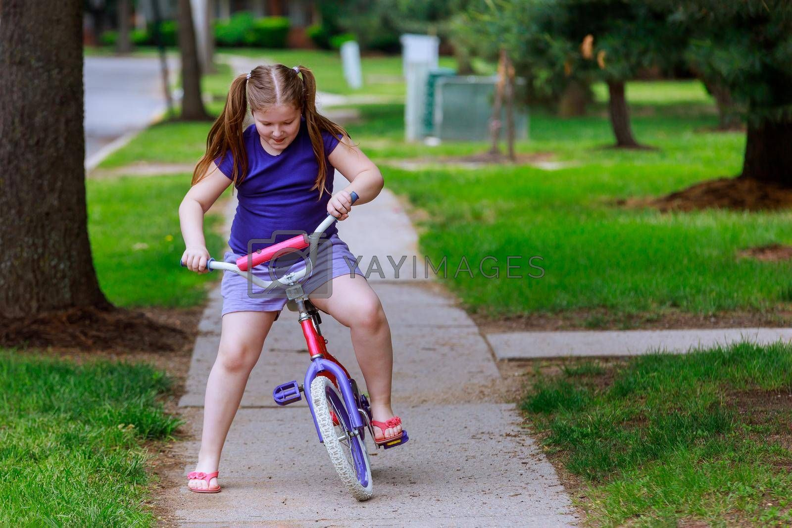 Little girl is biking the in the summer park on a city