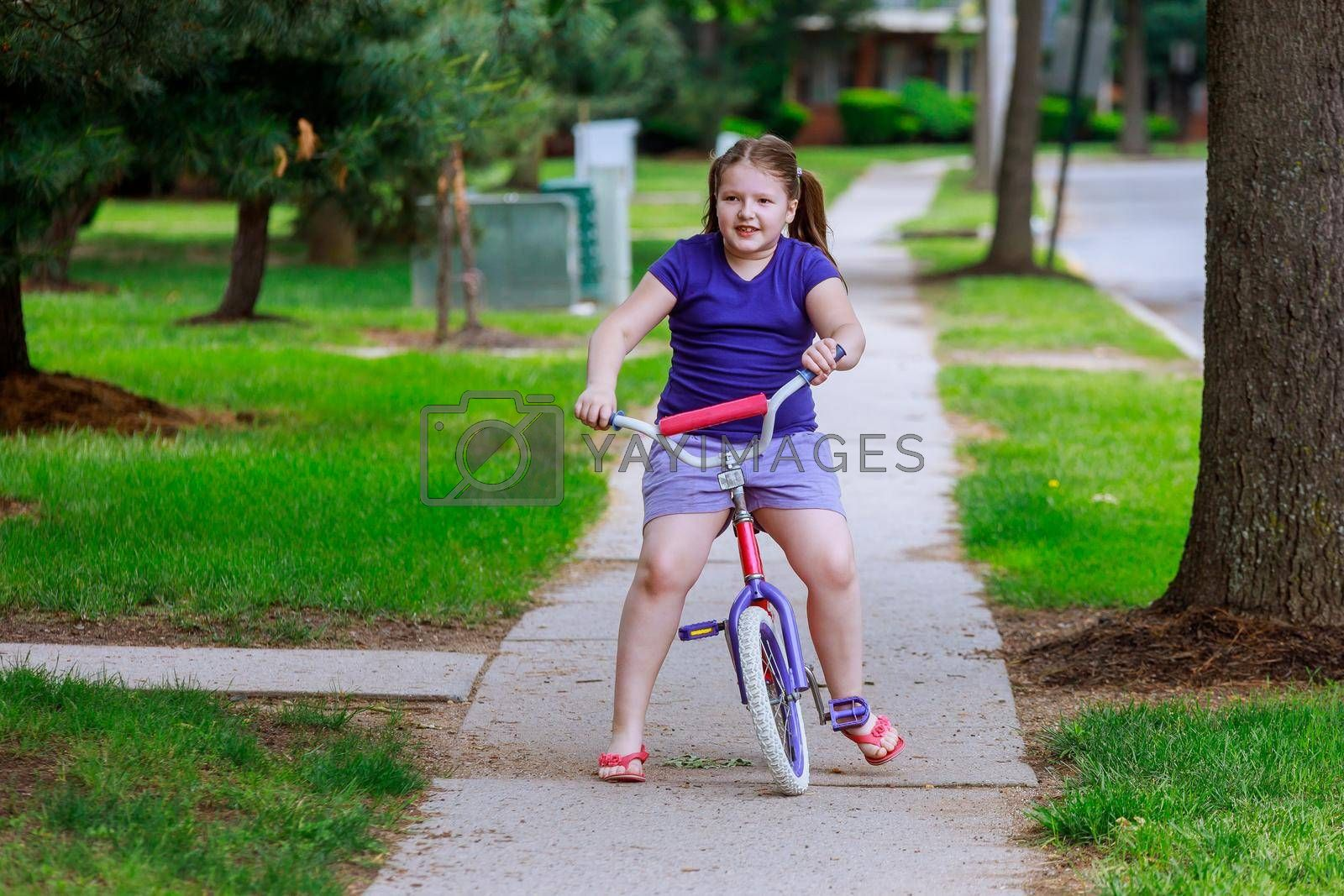 Beautiful little girl smiling is riding the bicycle in the park on a city