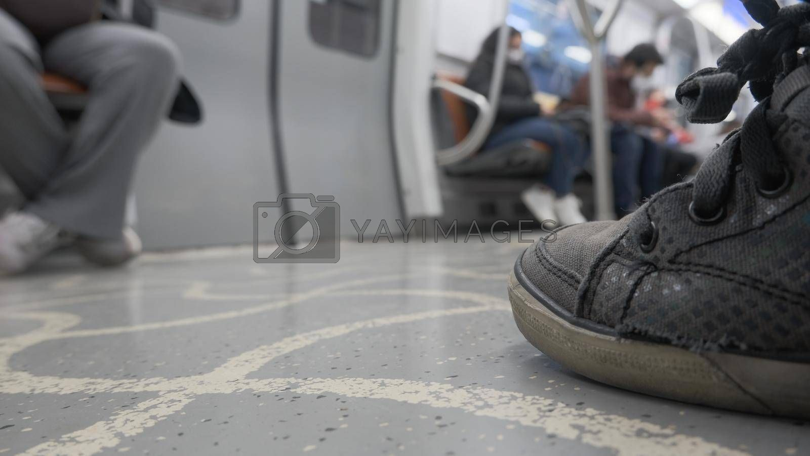 It depicts a low angle view of subway passengers sitting