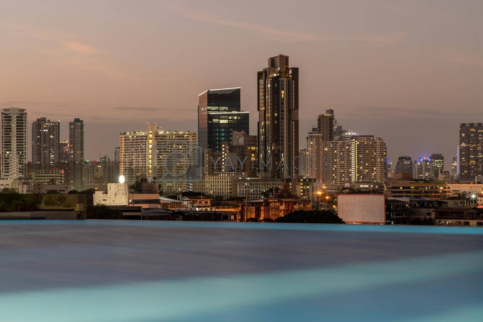 Bangkok, thailand - Dec 30, 2020 : Silhouette of Bangkok city skylines with light reflection in swimming pool during sunset. Selective focus.