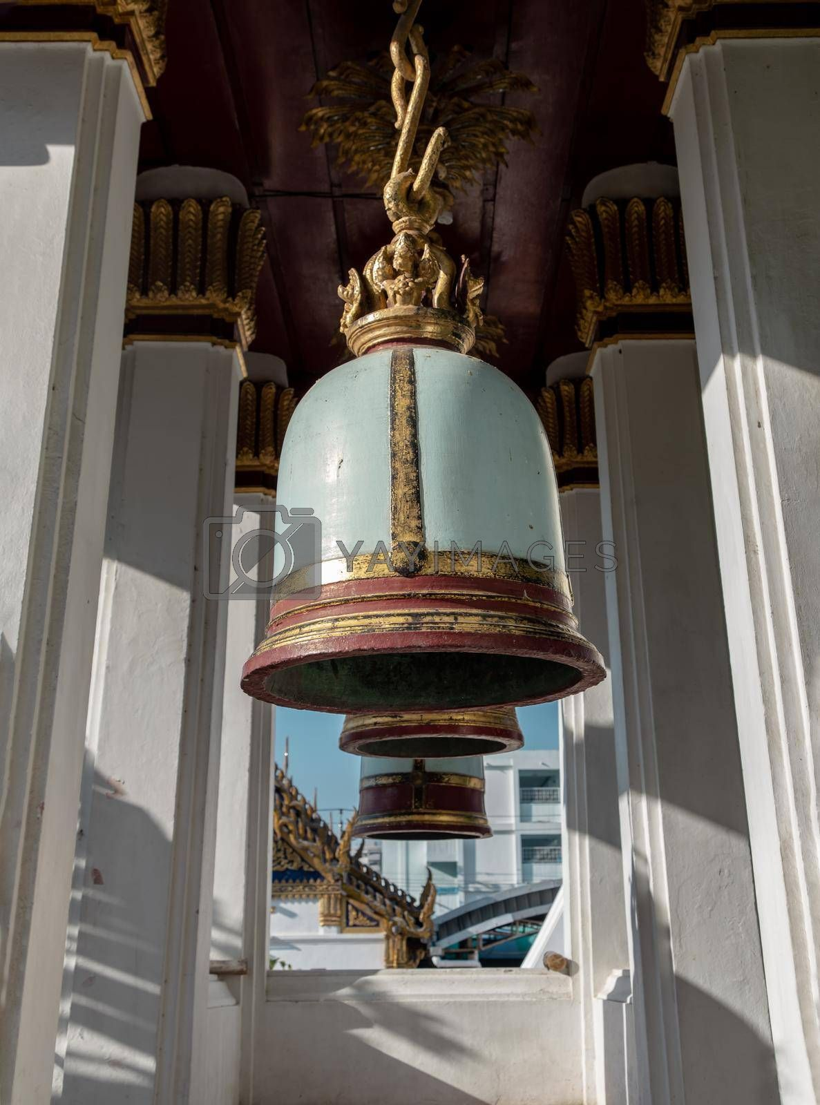 Ancient bells hanging on pillars outside in the thai temple. Thai temple bell which believe that who knock this bell will get the good luck, Selective focus.